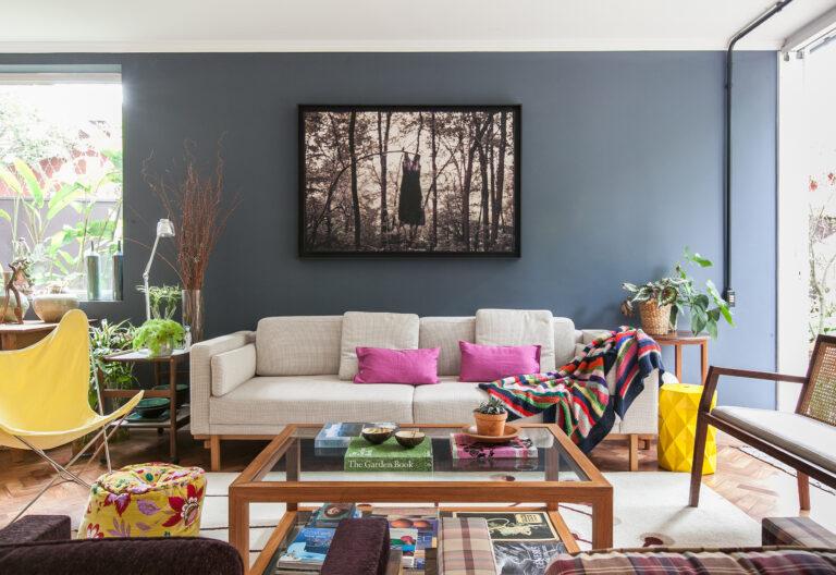 Sala com parede escura e móveis coloridos