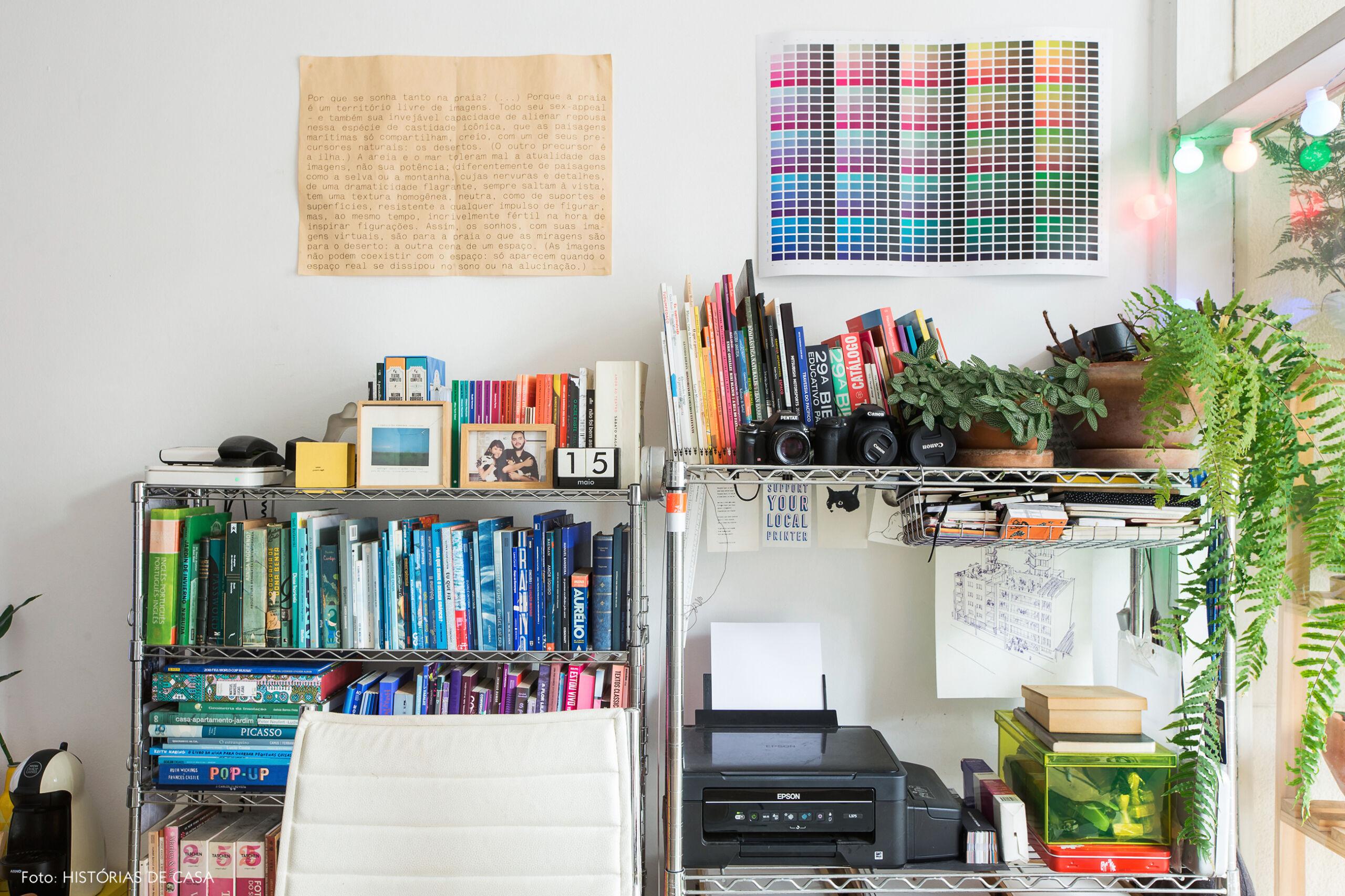 Escritório com estantes metálicas e livros organizados por cor