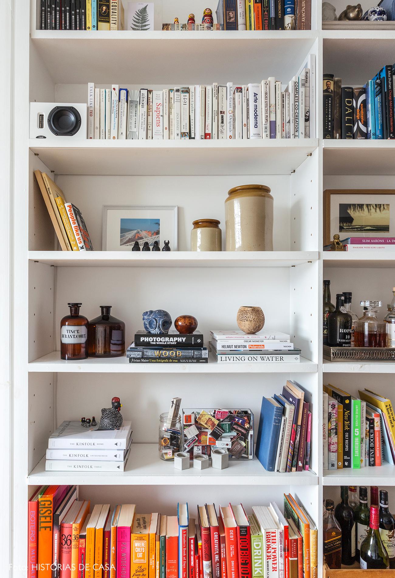 Estante branca decorada com objetos de viagem e livros coloridos