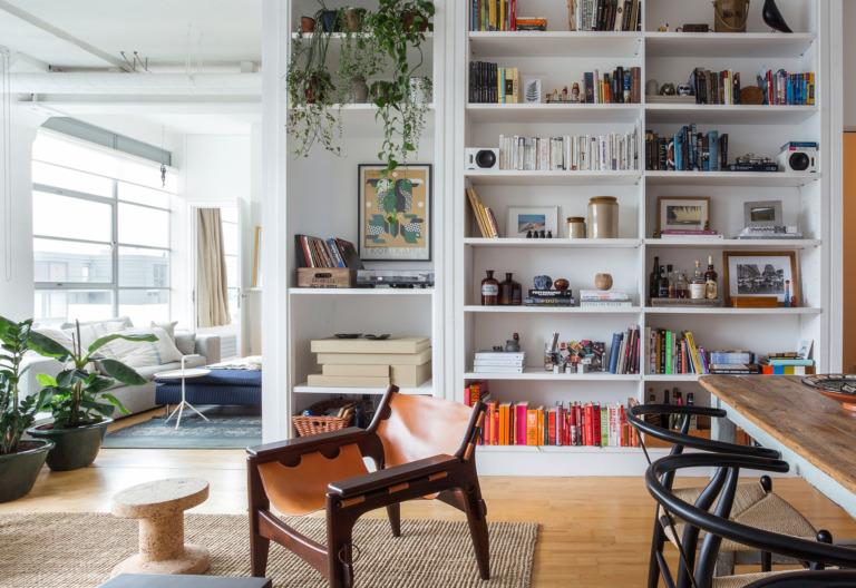 Apartamento com estante embutida, plantas e móveis vintage