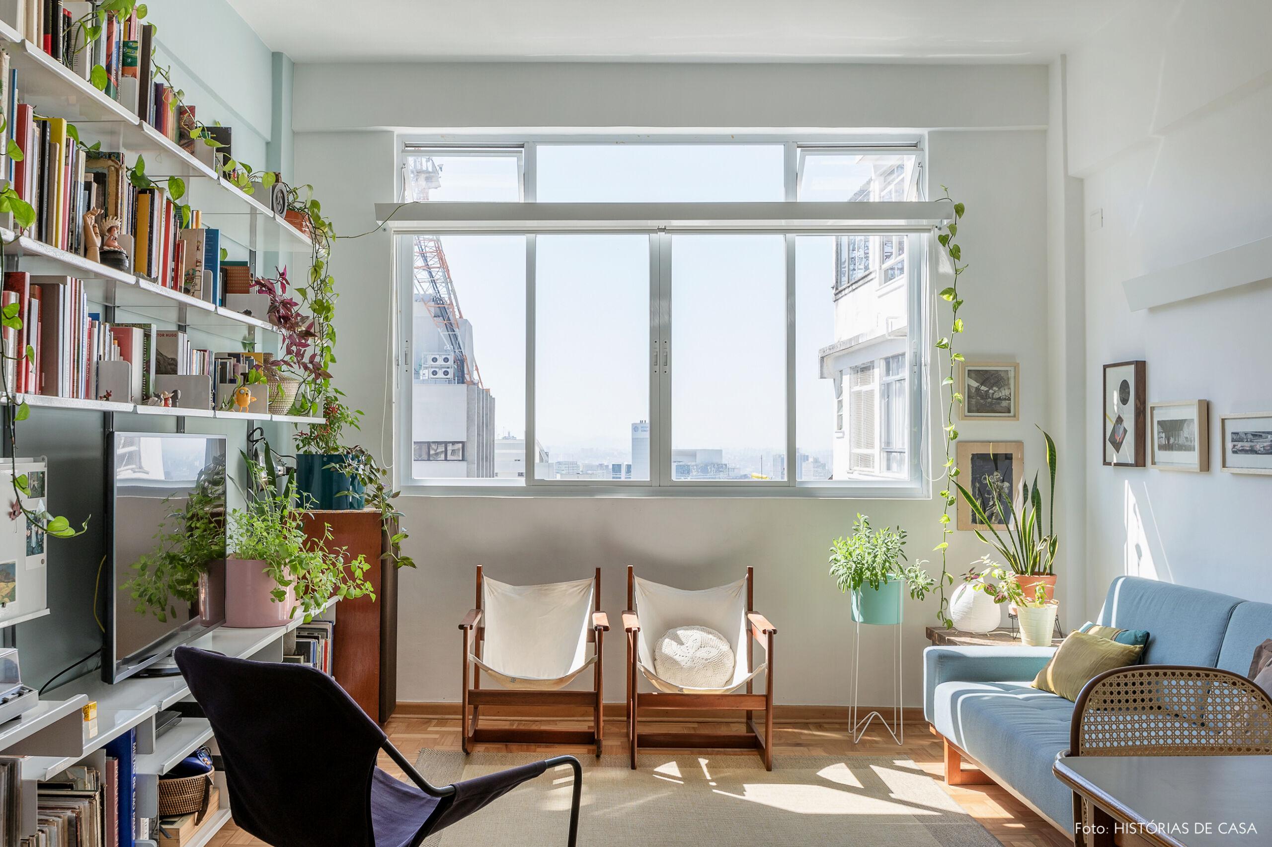 Sala pequena com sofá colorido e muitas plantas