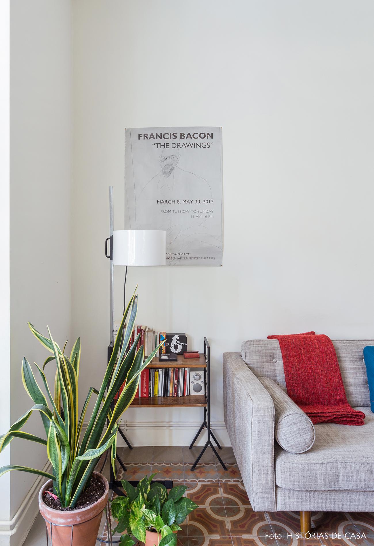 Sala com sofá cinza e piso de ladrilhos hidráulicos
