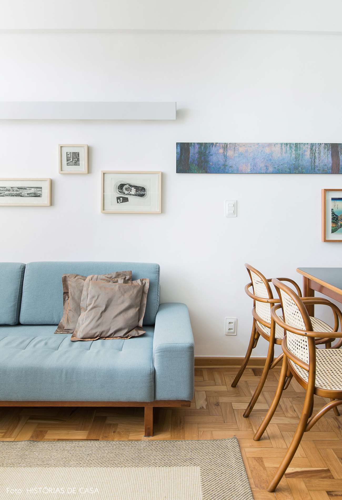 Sala pequena com sofá colorido, azul e parede de quadros