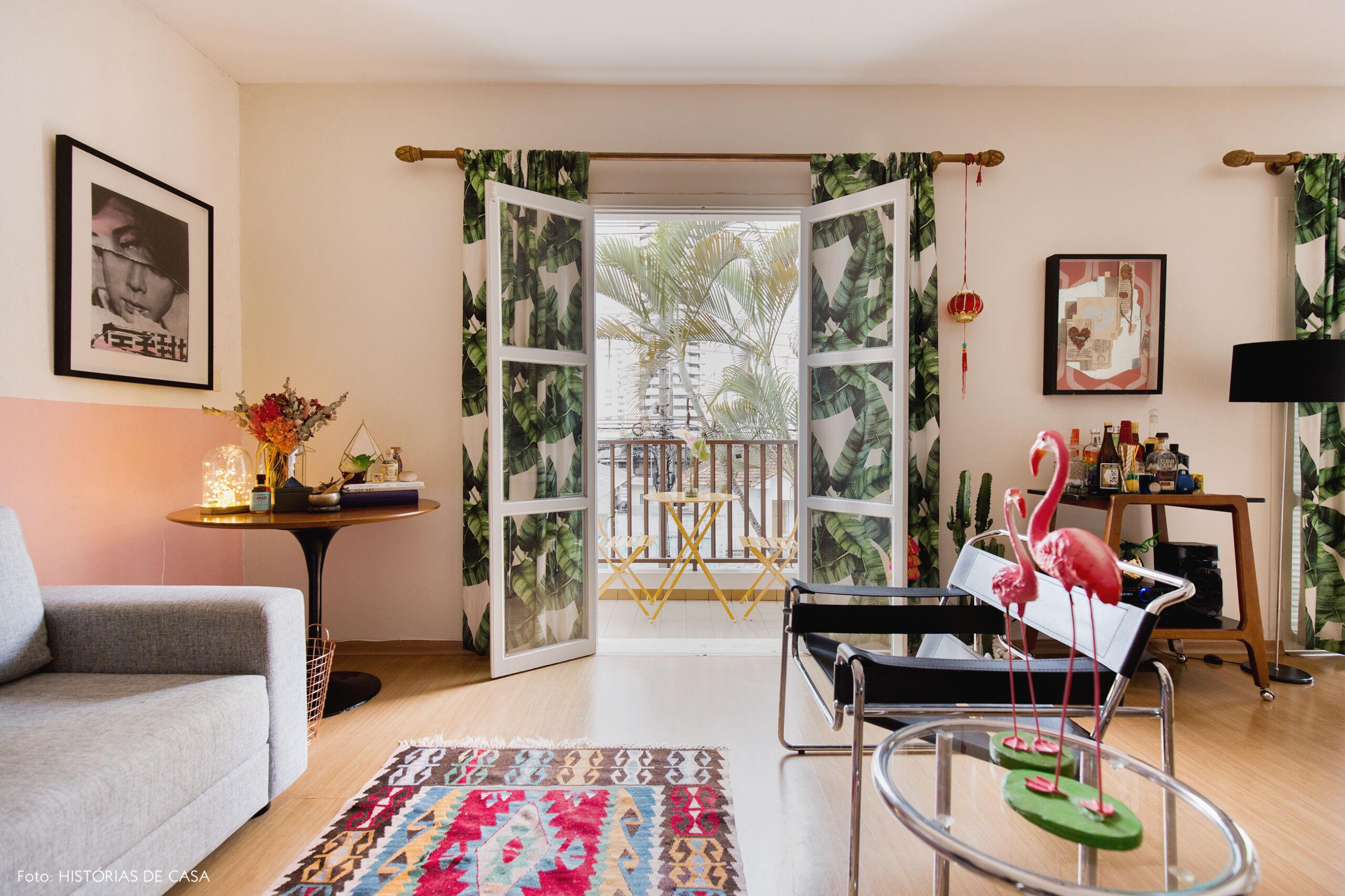 Sala de apartamento com cortinas estampadas com folhagens
