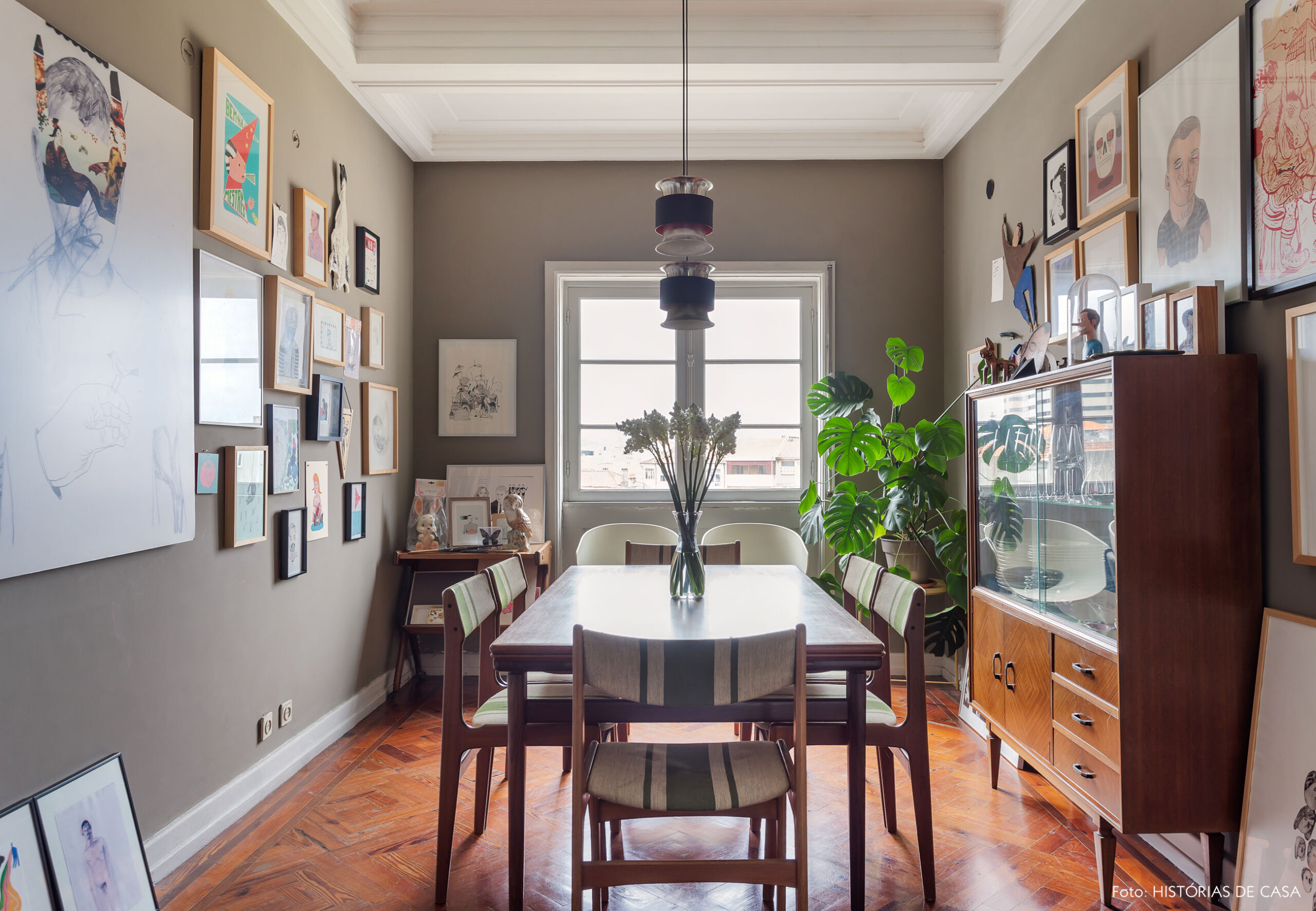 Sala de jantar com muitos quadros e parede cinza