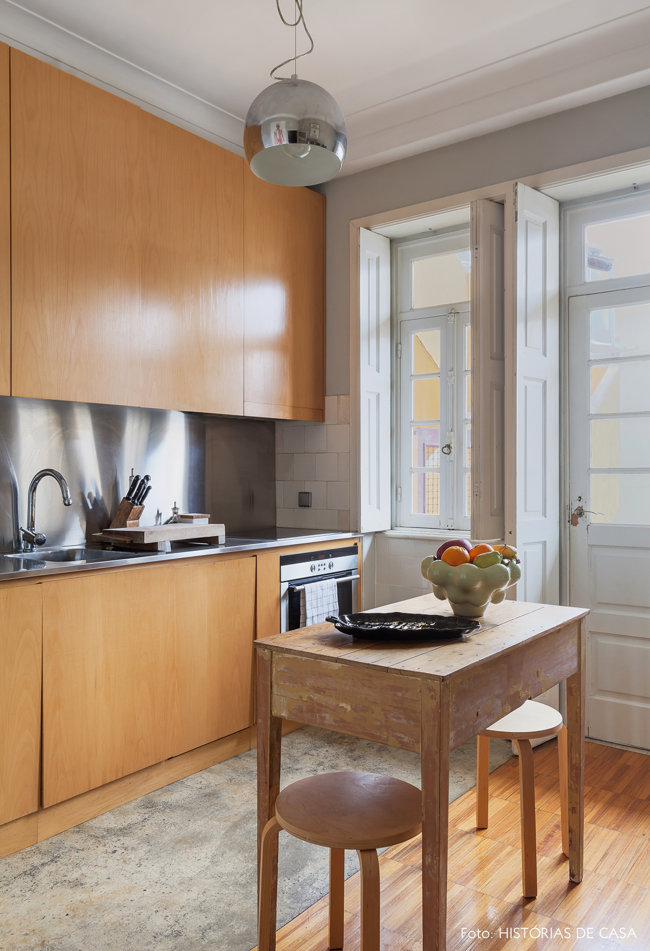 Cozinha reformada com mesa de madeira servindo de ilha central