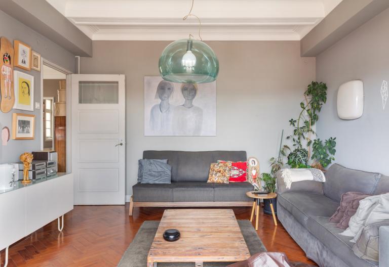 Sala de estar com parede e sofá cinza