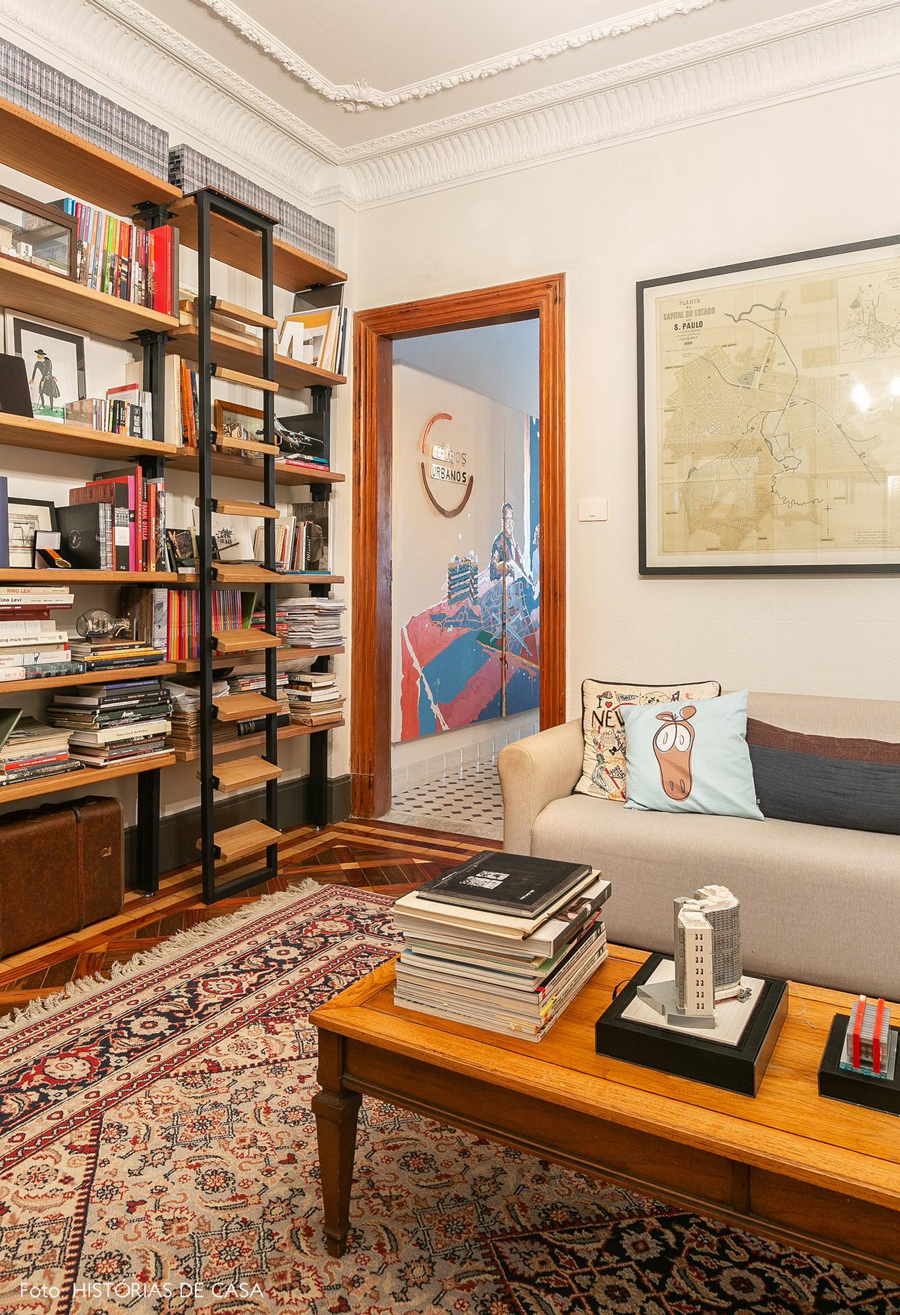 Estante do piso ao teto e sofá pequeno em escritório antigo
