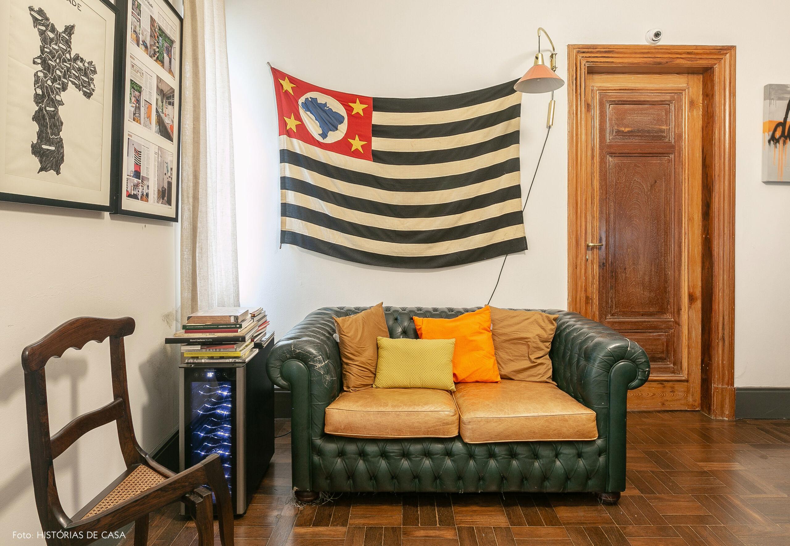 Sala com sofá capitonê e bandeira de São Paulo na parede