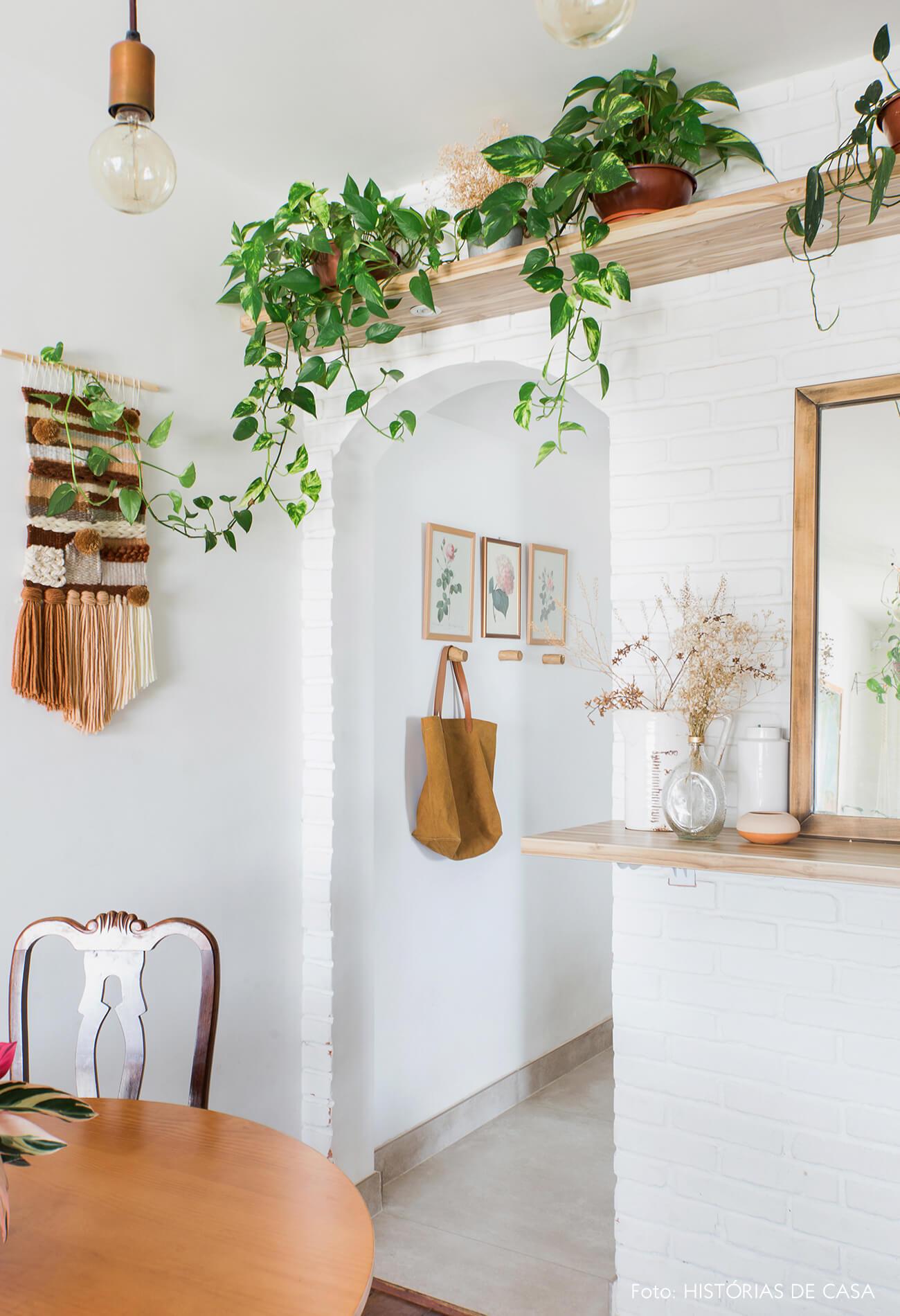 Apartamento pequeno com parede de tijolinho branco e plantas