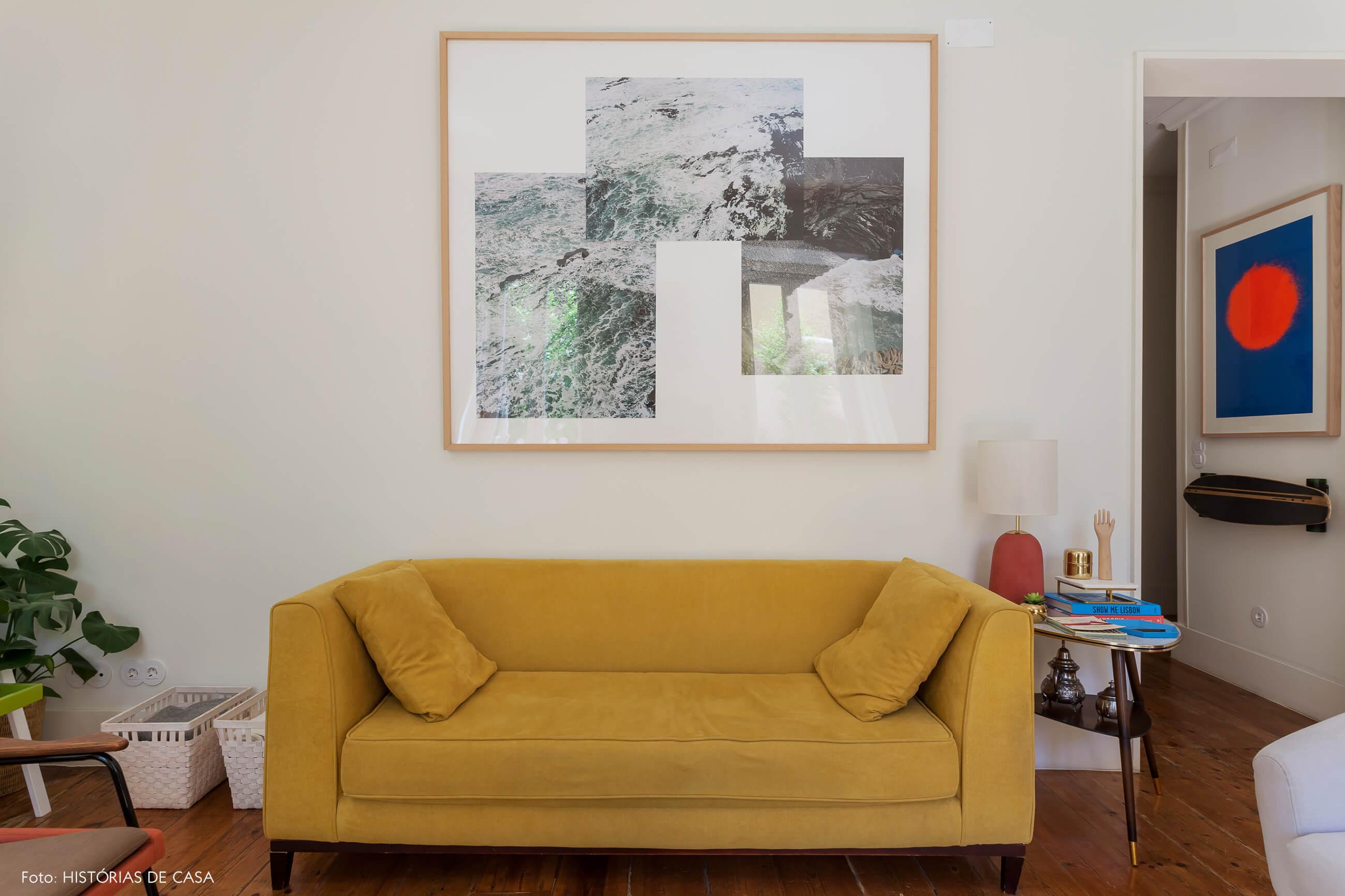 Sofá mostarda na sala com quadro preto e branco