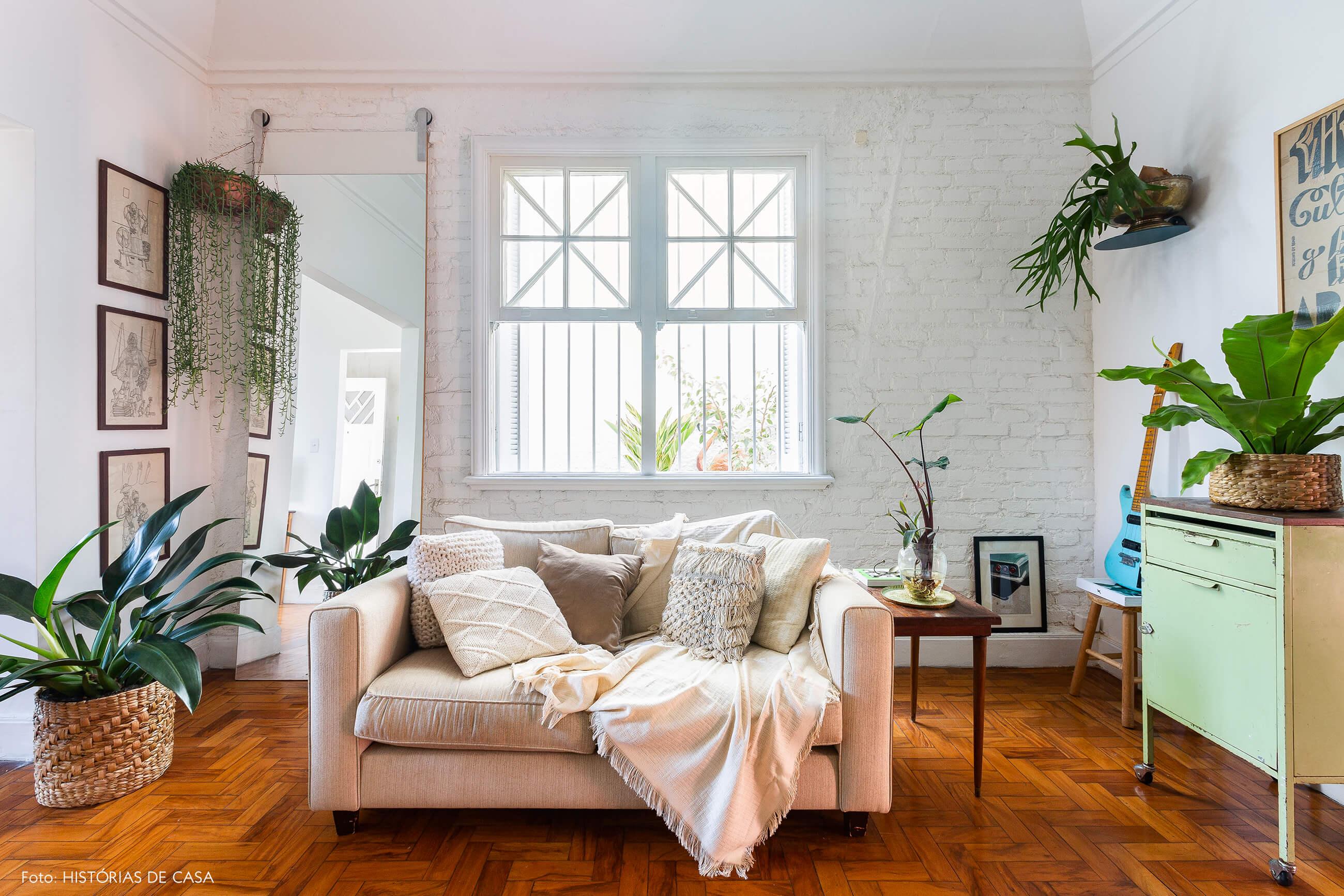 Casa de vila com salas integradas, sofá bege e muitas plantas