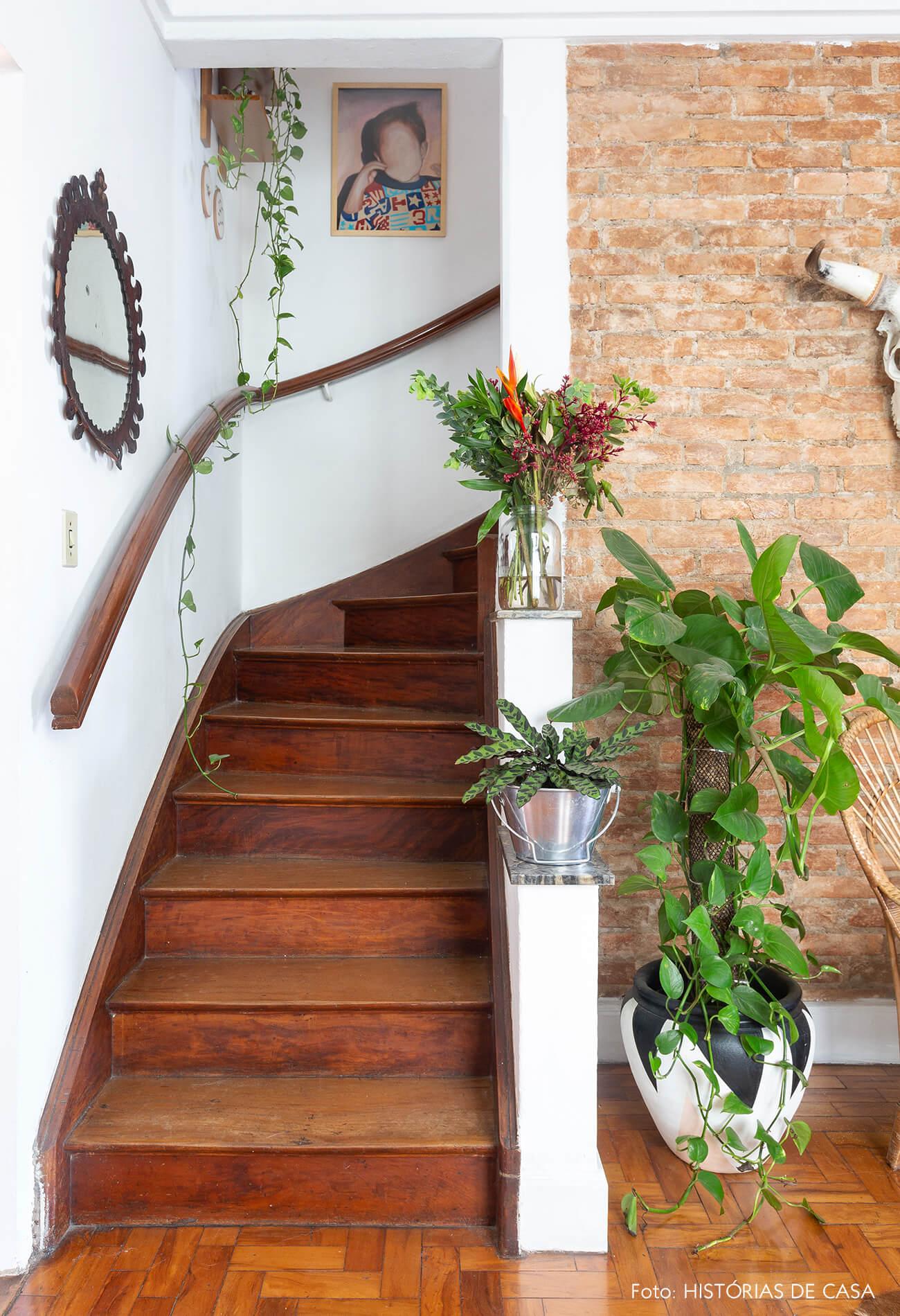 Escada antiga de madeira com plantas e parede de tijolinho