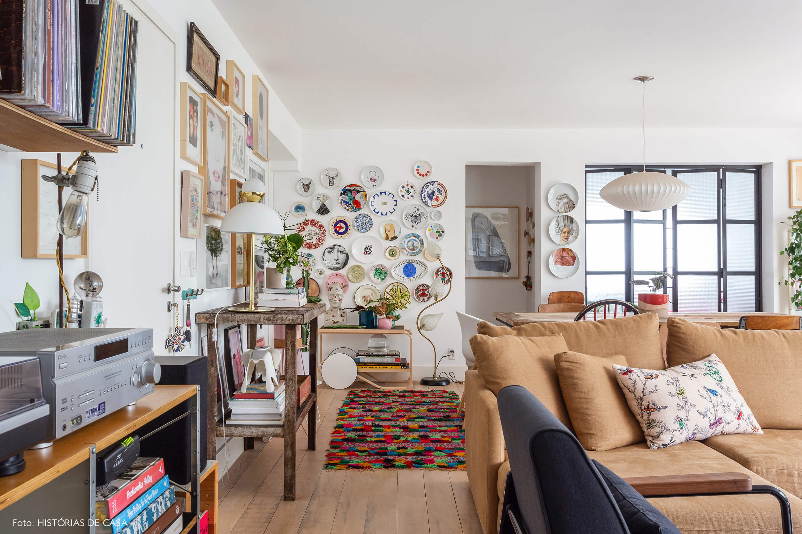 Sala com muitos quadros e sofá em tom caramelo