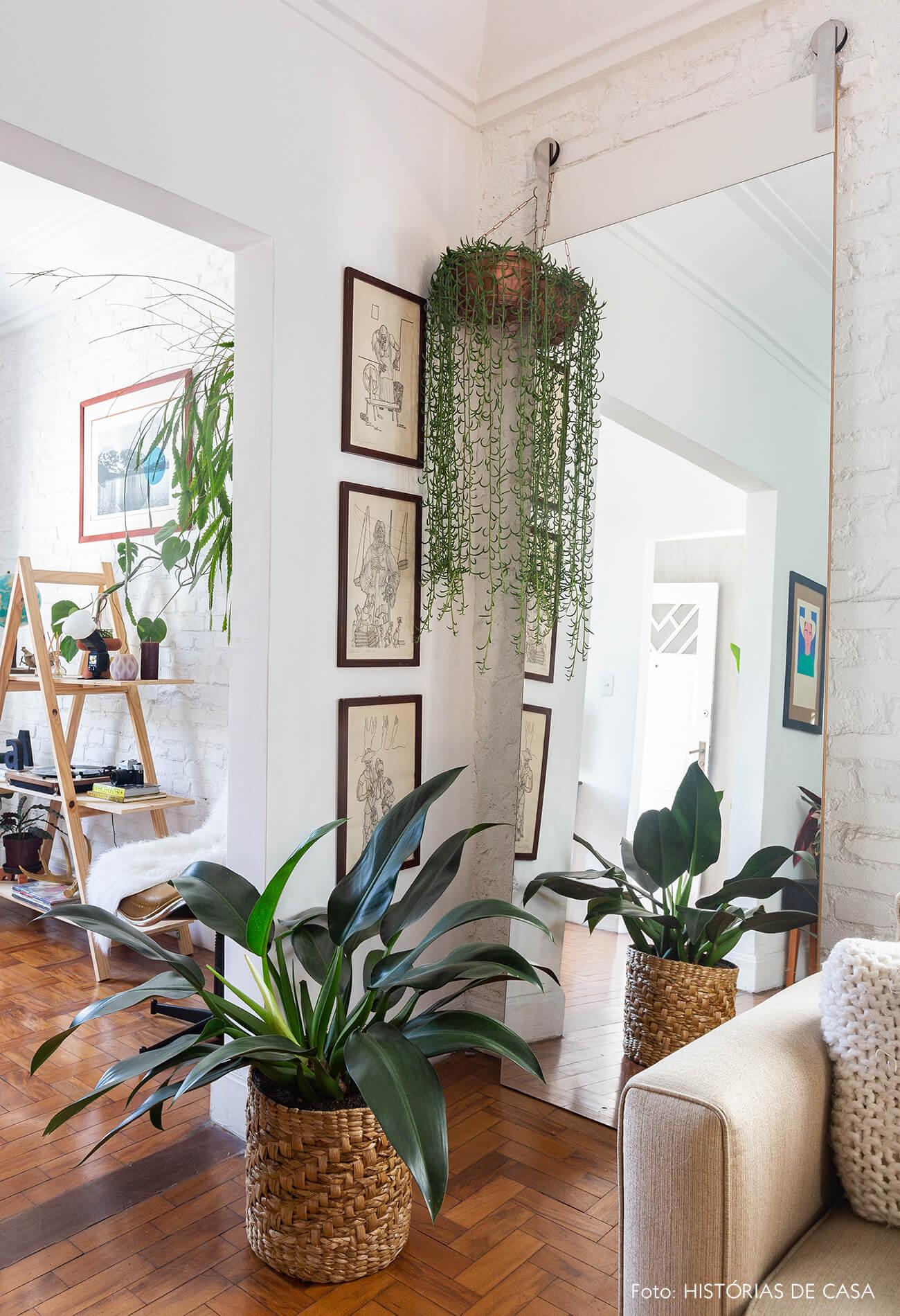 Canto da sala com parede de tijolinho, espelho e planta pendente