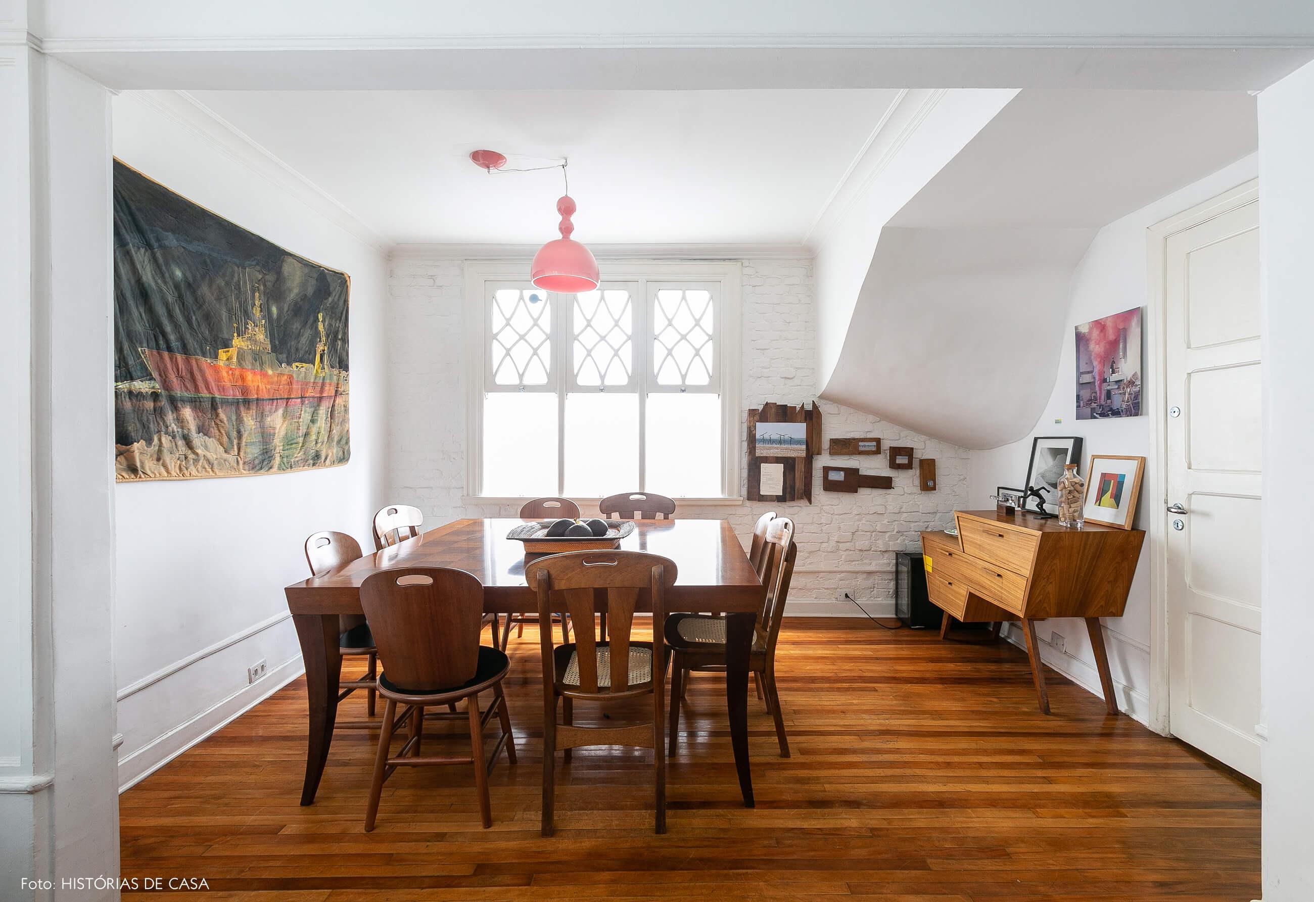 Sala de jantar com móveis de madeira e pendente rosa