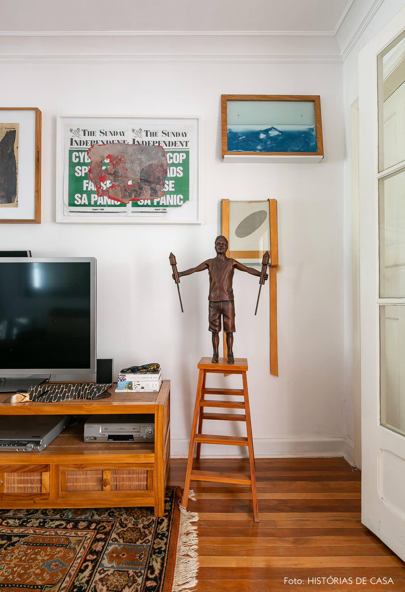 Sala com sofá de couro marrom e obras de arte