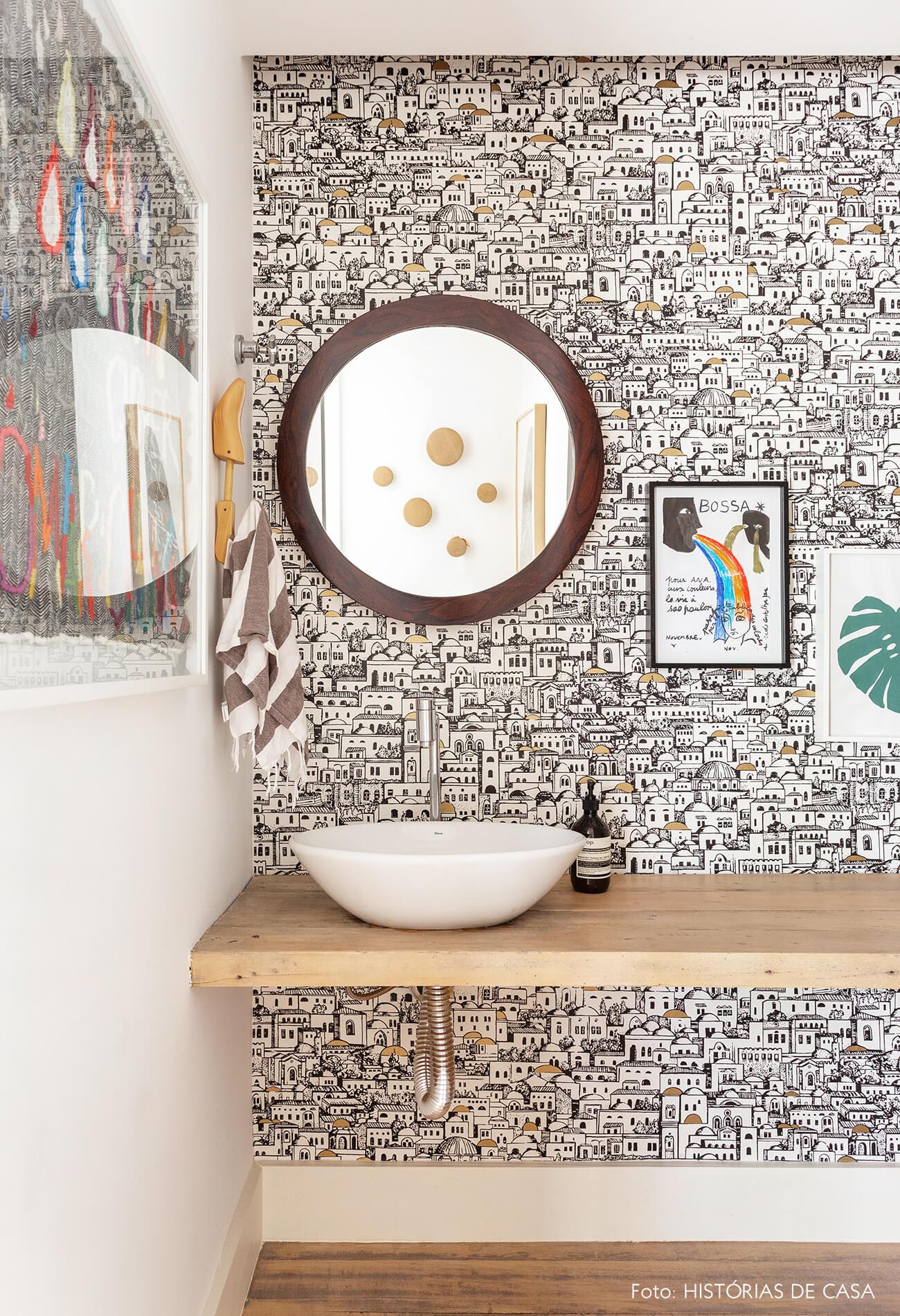 Lavabo com papel de parede e espelho redondo