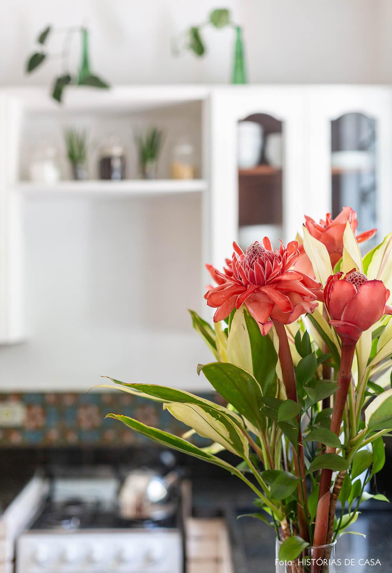 Cozinha de casa antiga com piso de ladrilhos e arranjo de flores