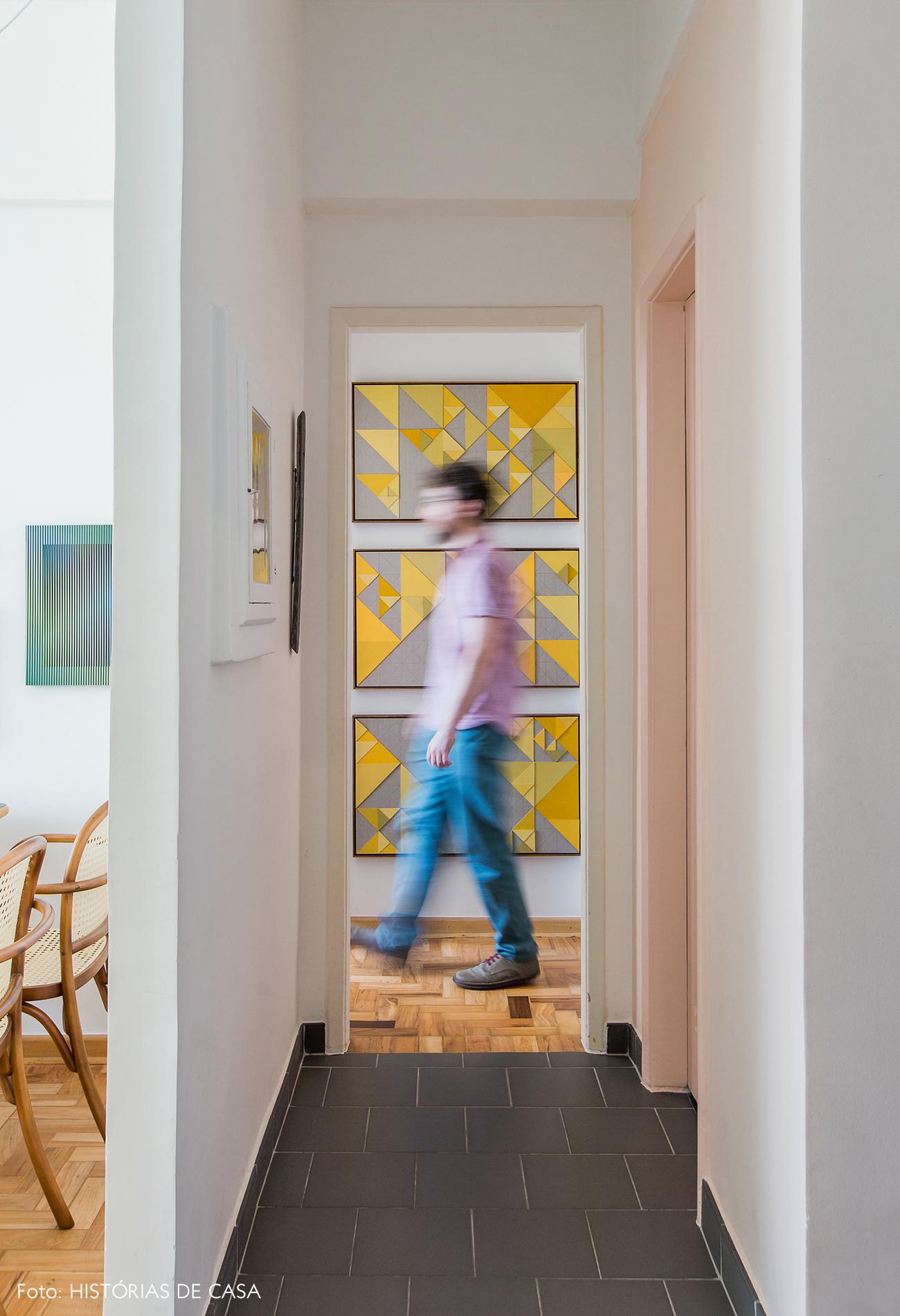 Corredor com piso cinza e quadros amarelos