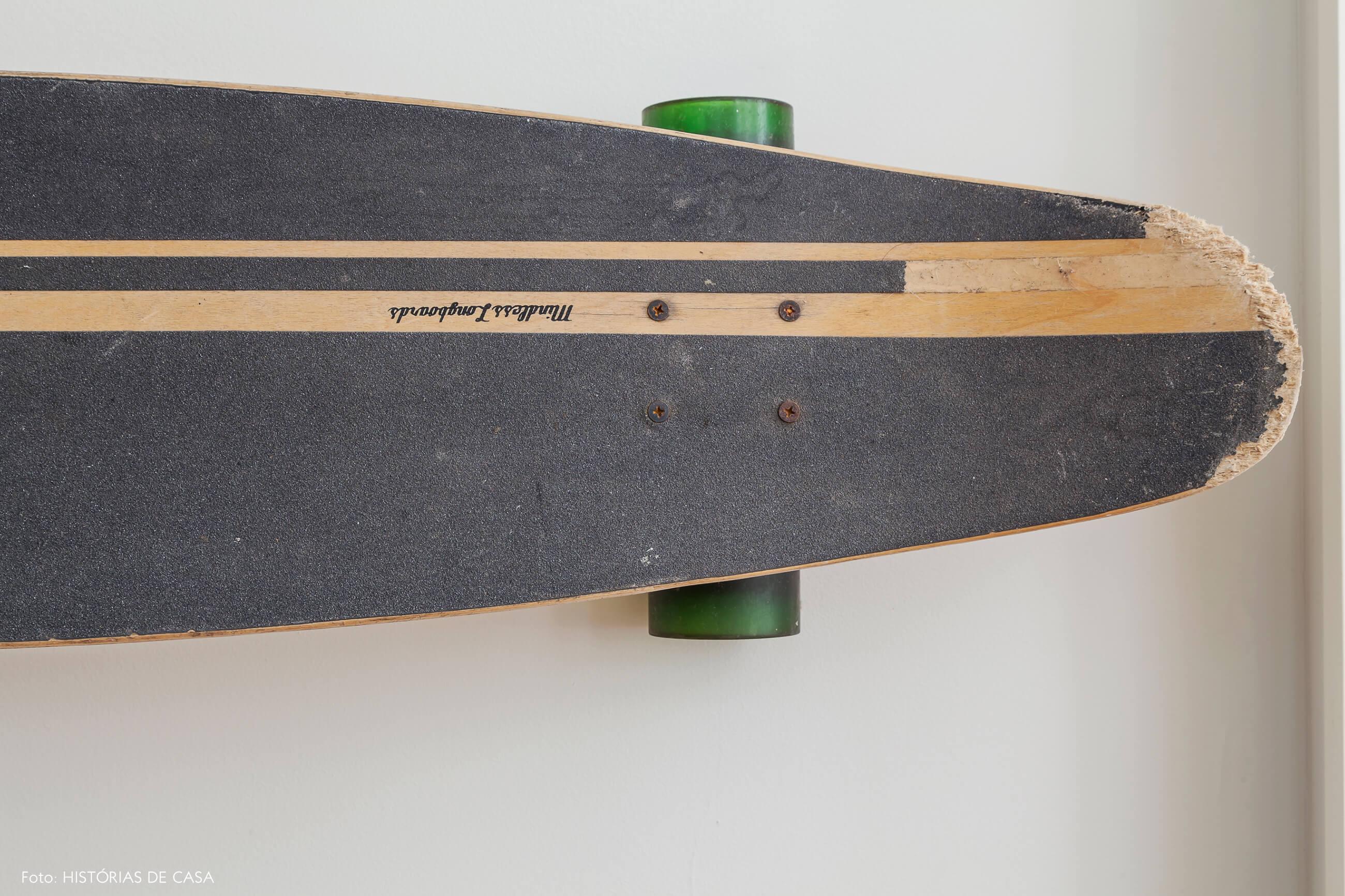 Skate pendurado na parede sob quadros