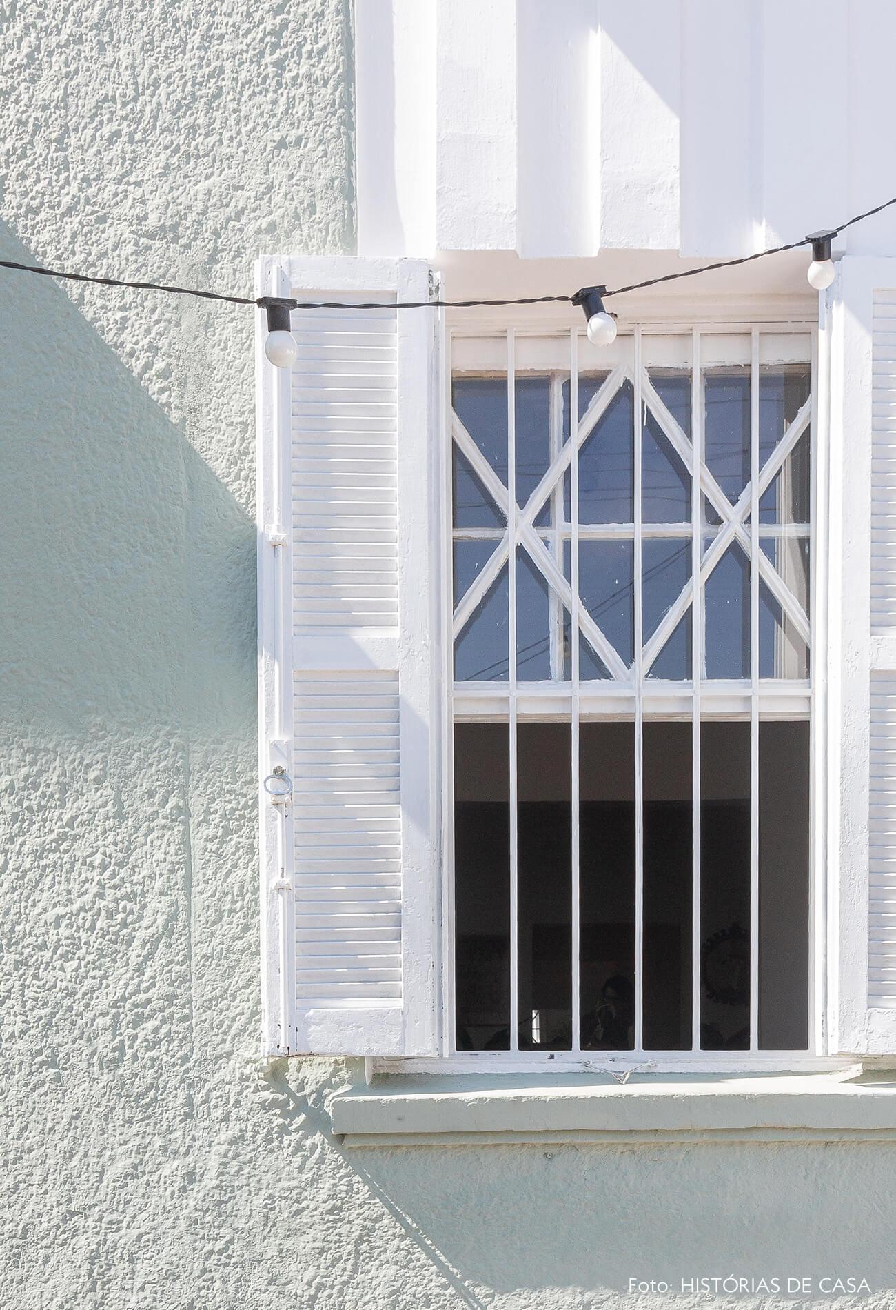 Casa de vila com janela antiga pintada de branco