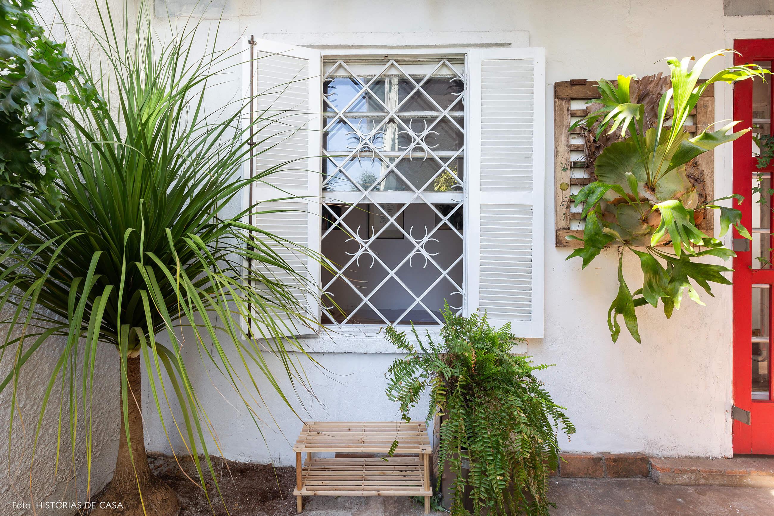 Casa de vila com janelas antigas e muitas plantas