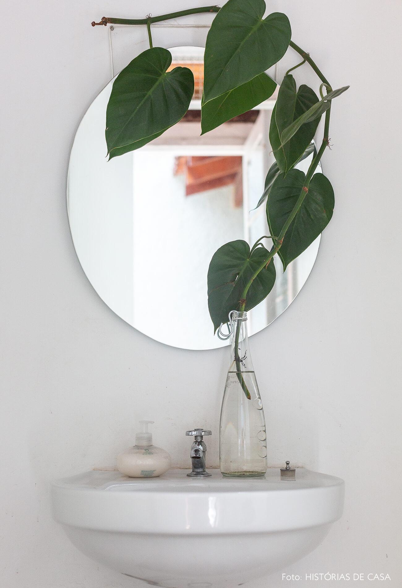 Banheiro com espelho redondo e plantas na água
