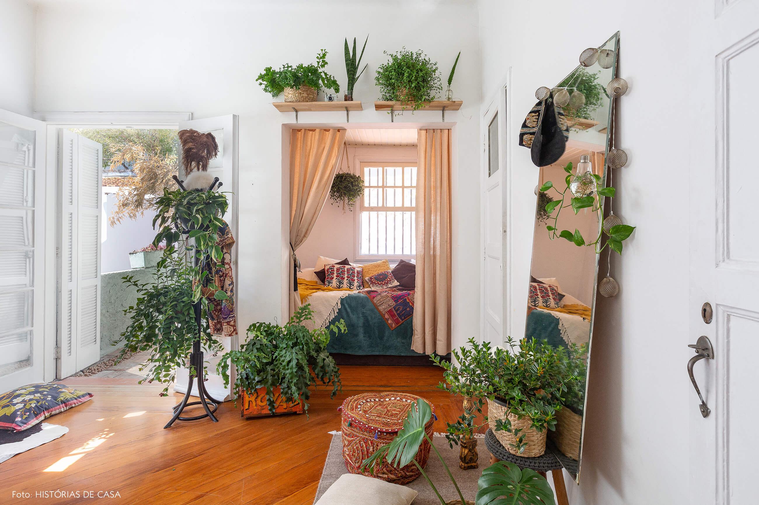 Quarto com tenda estilo étnica e muitas plantas