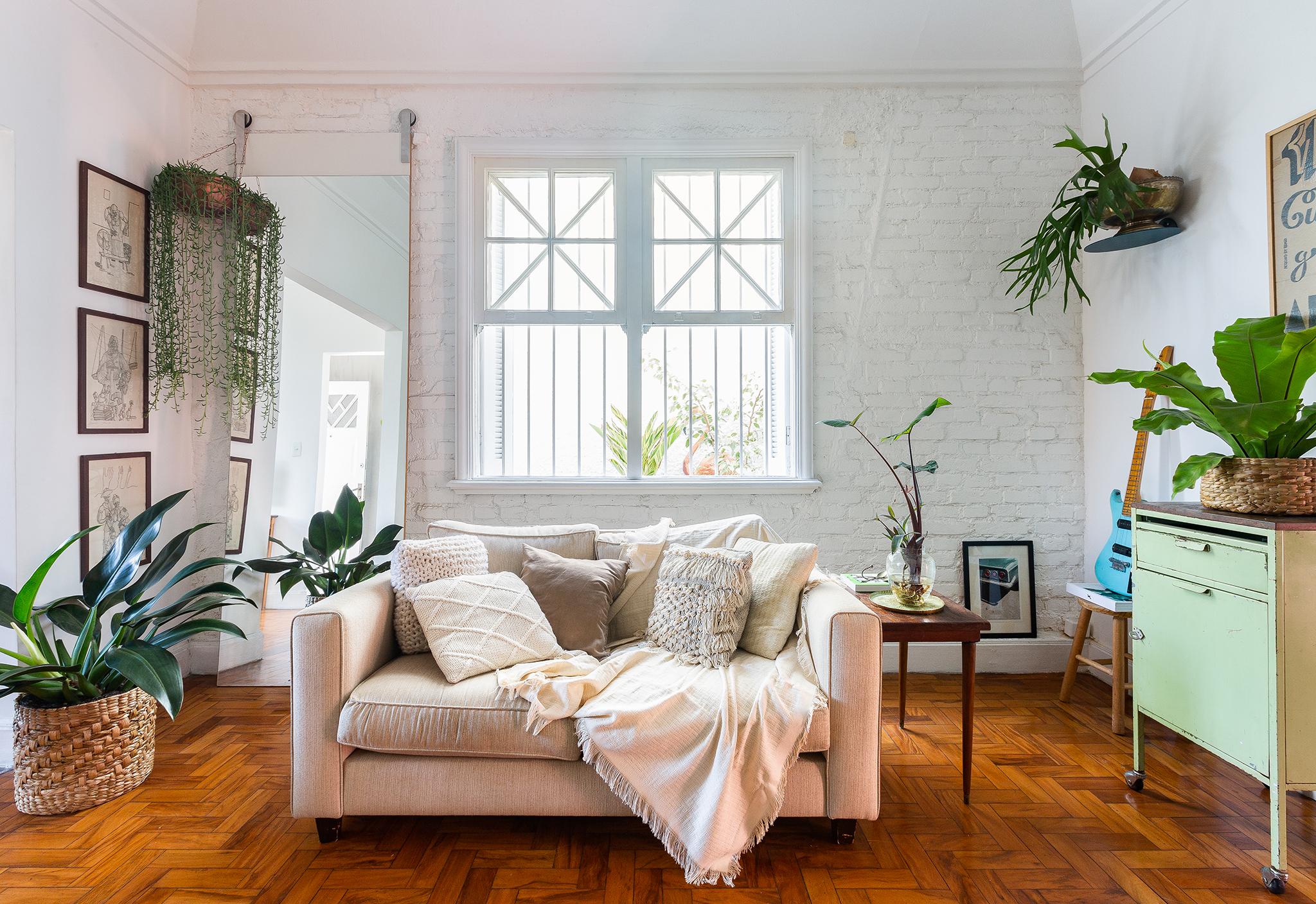 Sala com parede de tijolinho branco e muitas plantas