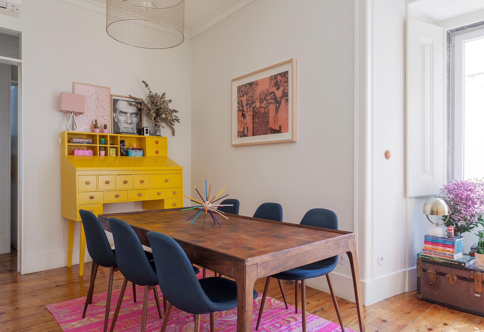 Sala de jantar com tapete rosa e móvel amarelo
