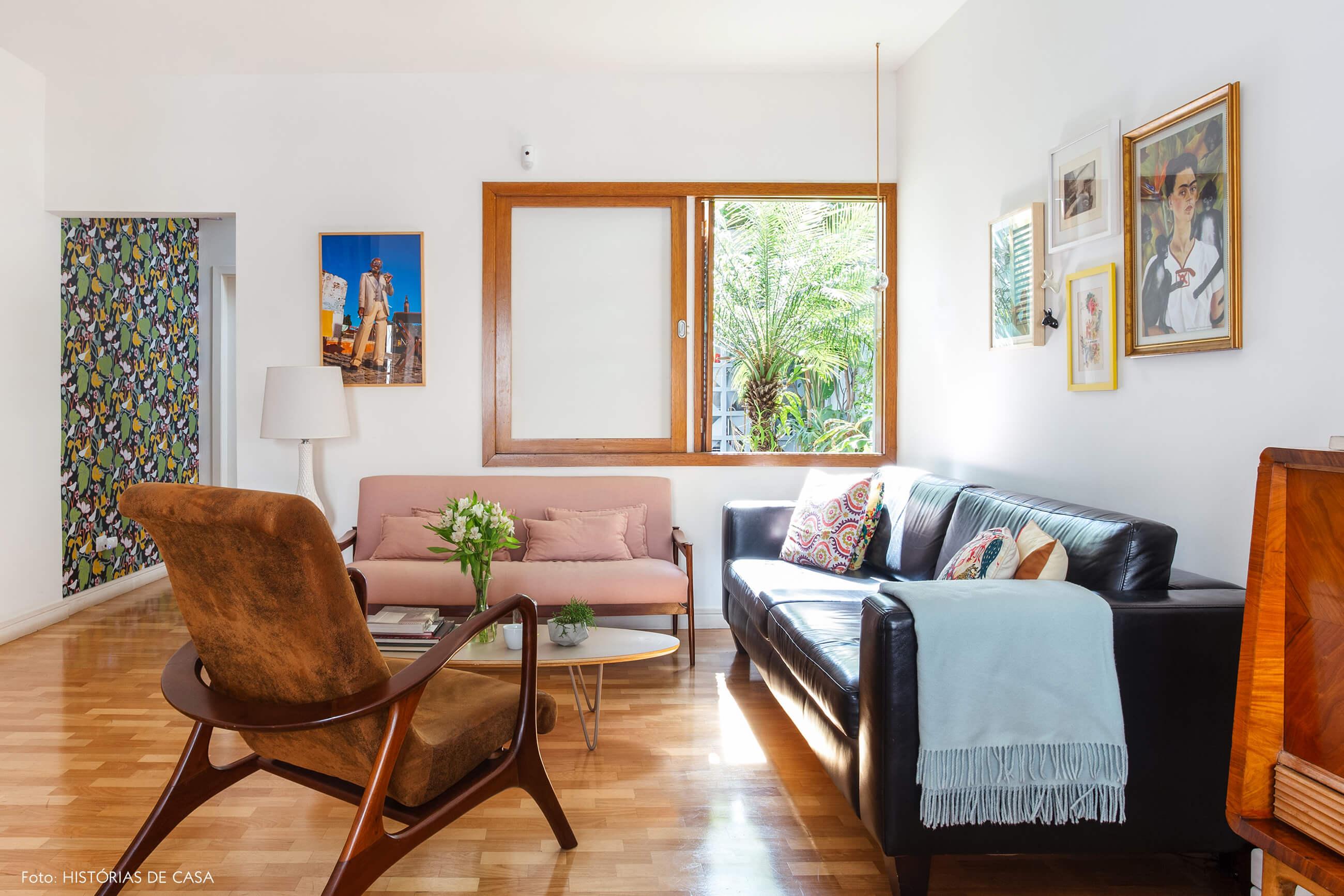 Sala com janelas de madeira e sofás rosa e preto