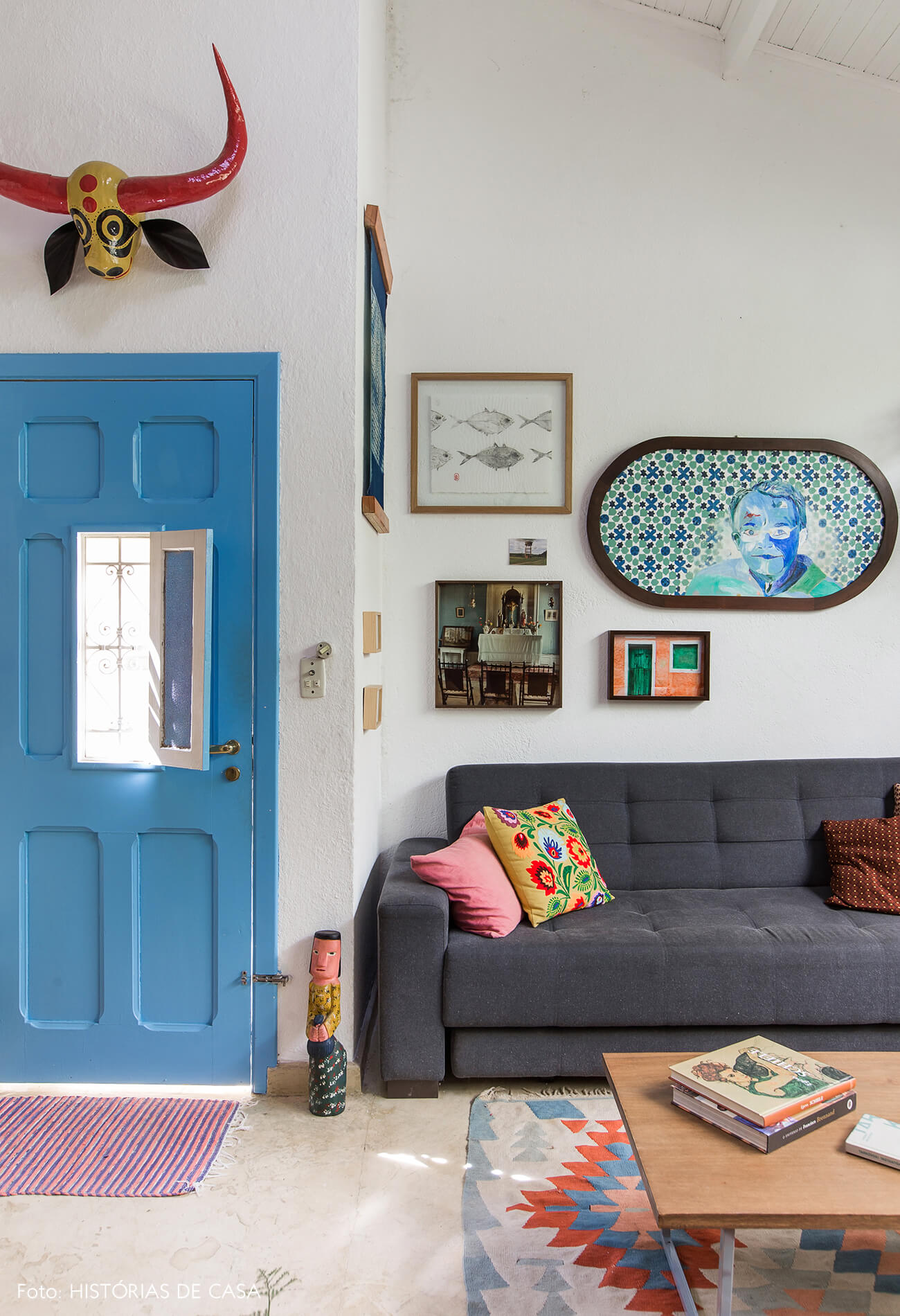 Sala bem colorida com porta azul e muitos quadros