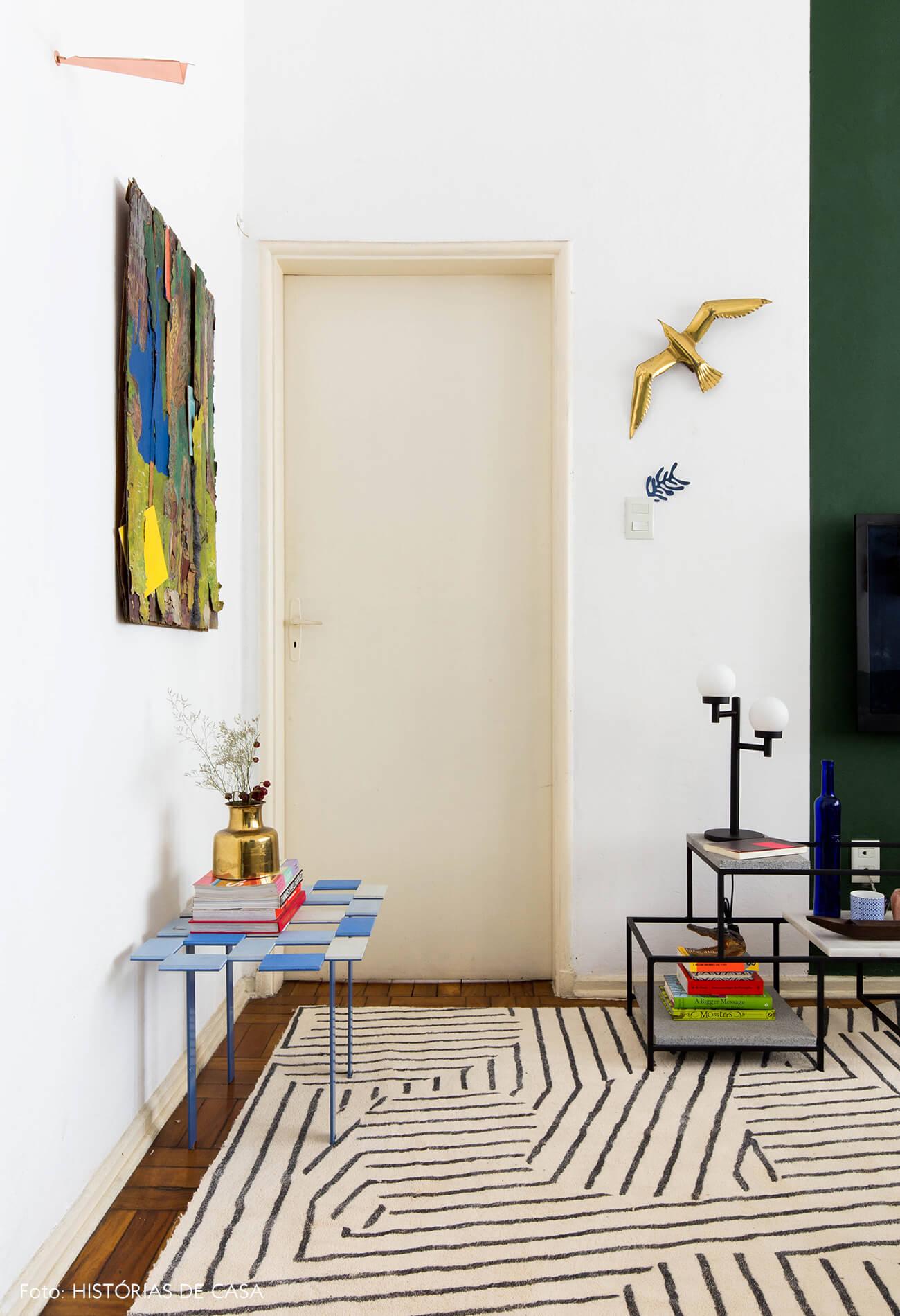 Sala com parede pintada de verde e tapete geométrico