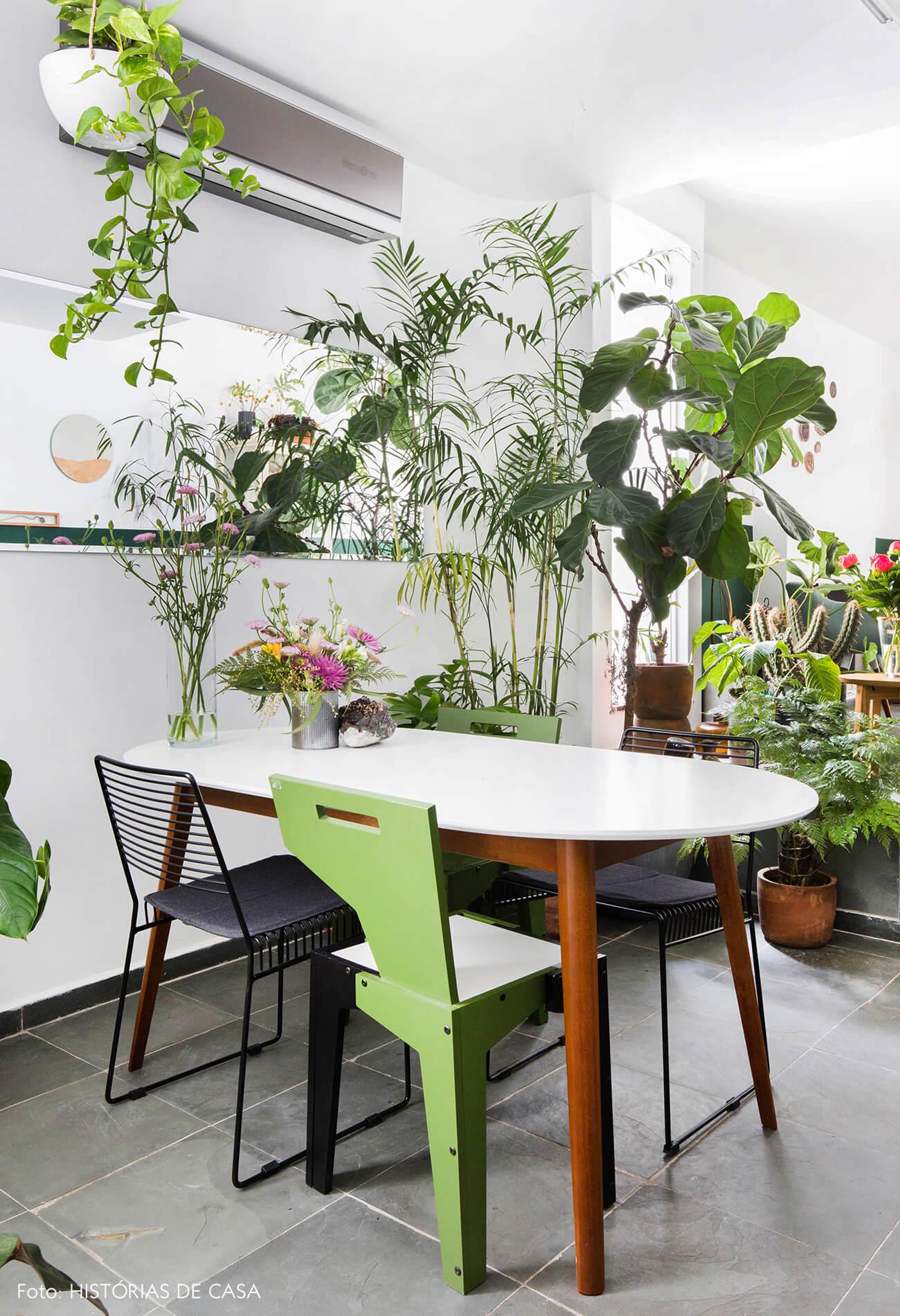 Sala de jantar com muitas plantas e piso cinza