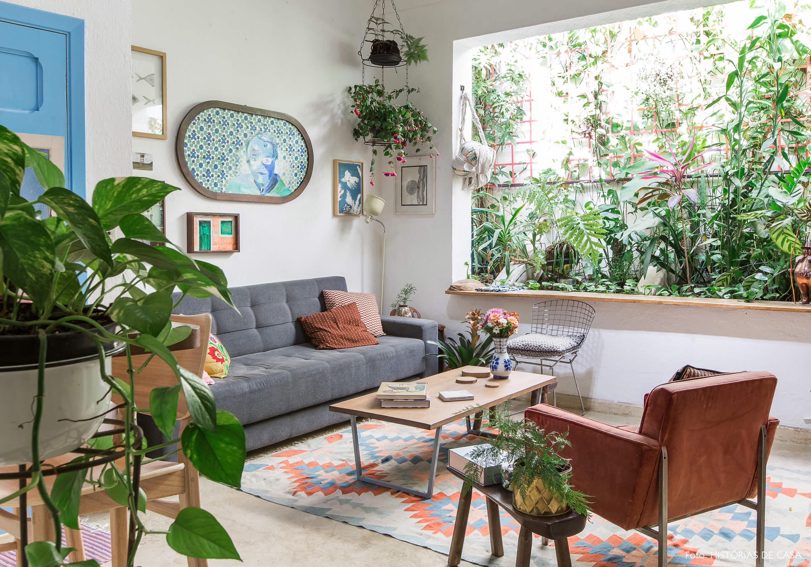 Sala colorida com sofá cinza e muitas plantas