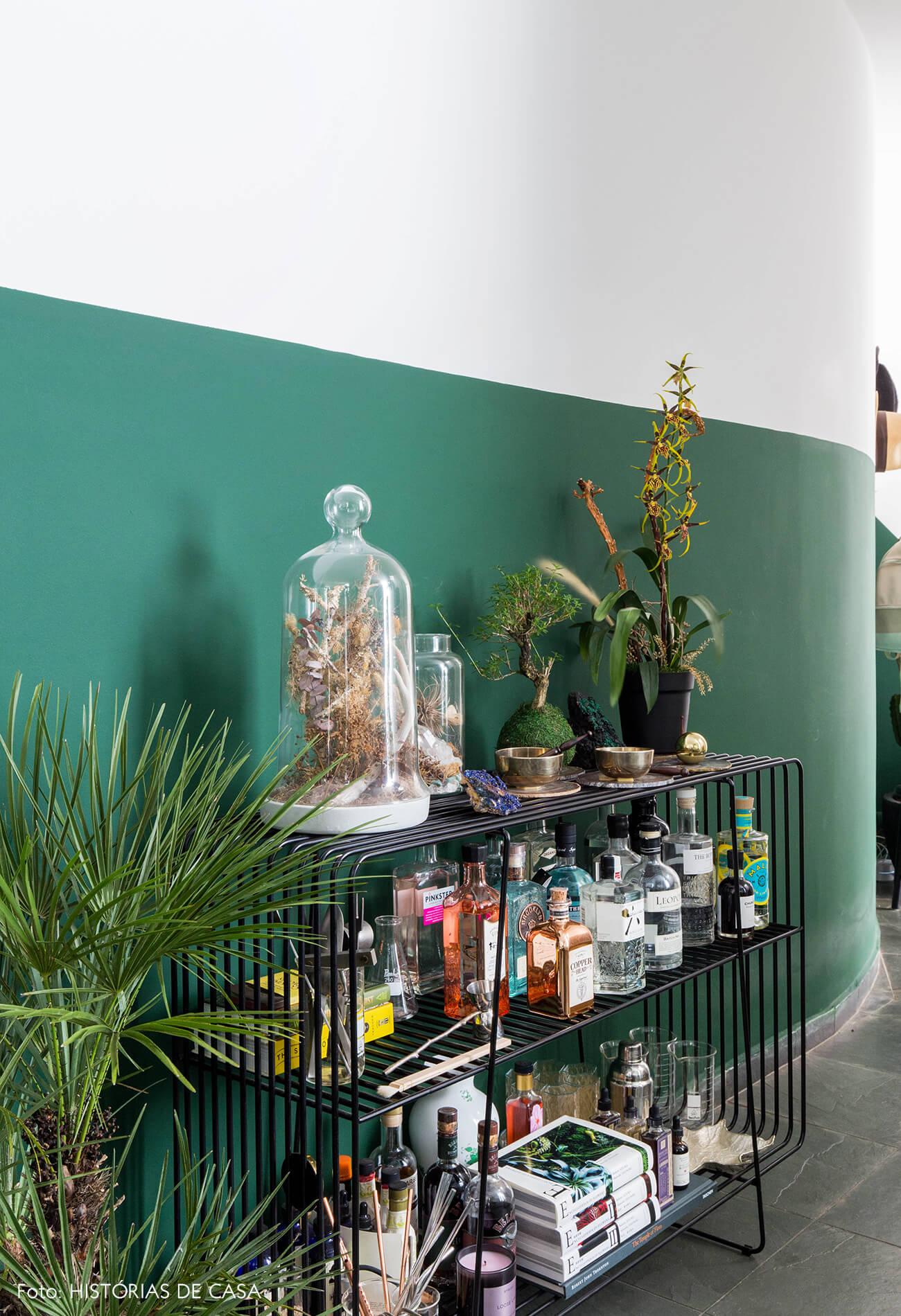 Meia parede verde e aparador como bar