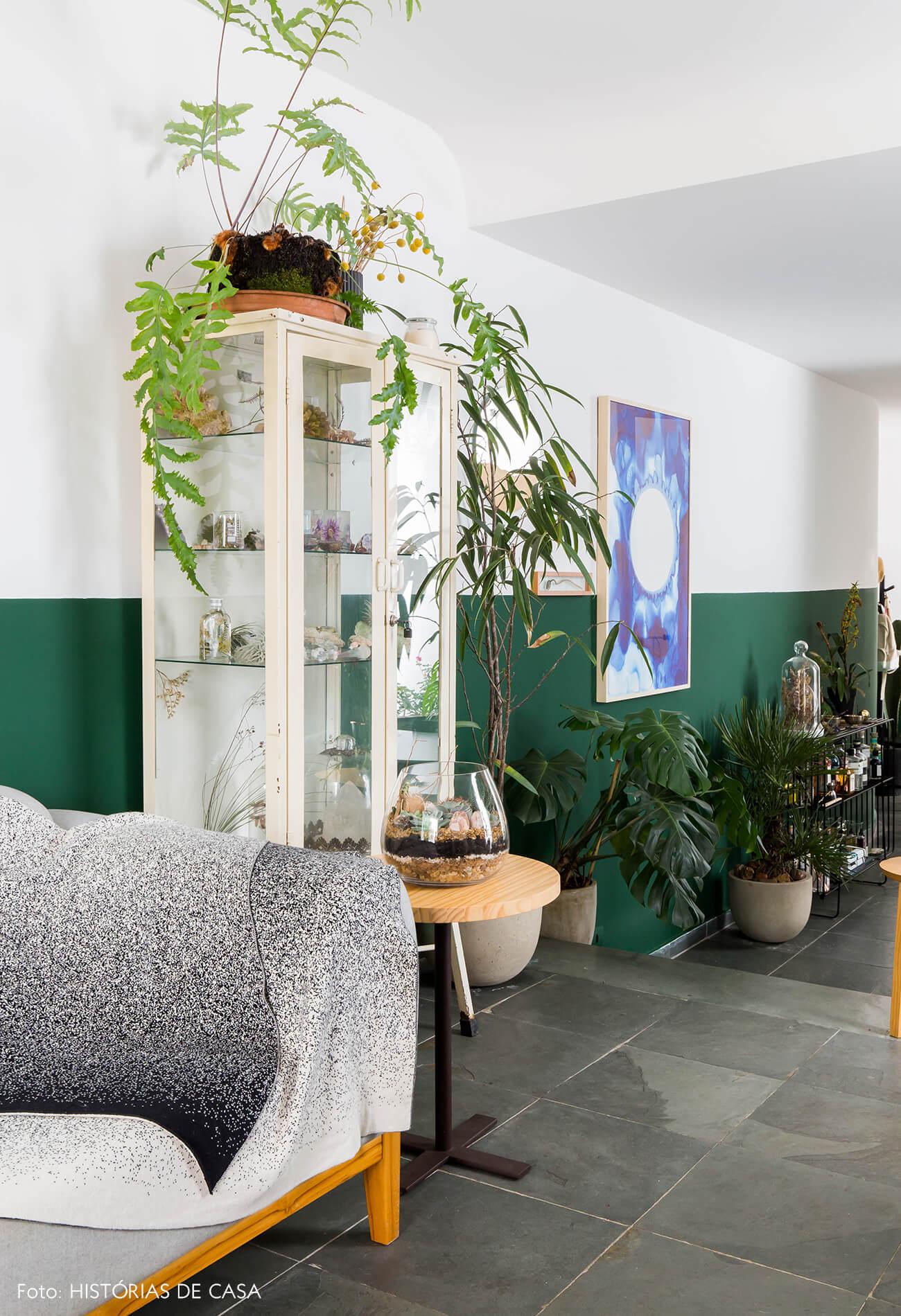 Sala com meia parede verde e armário de farmácia vintage