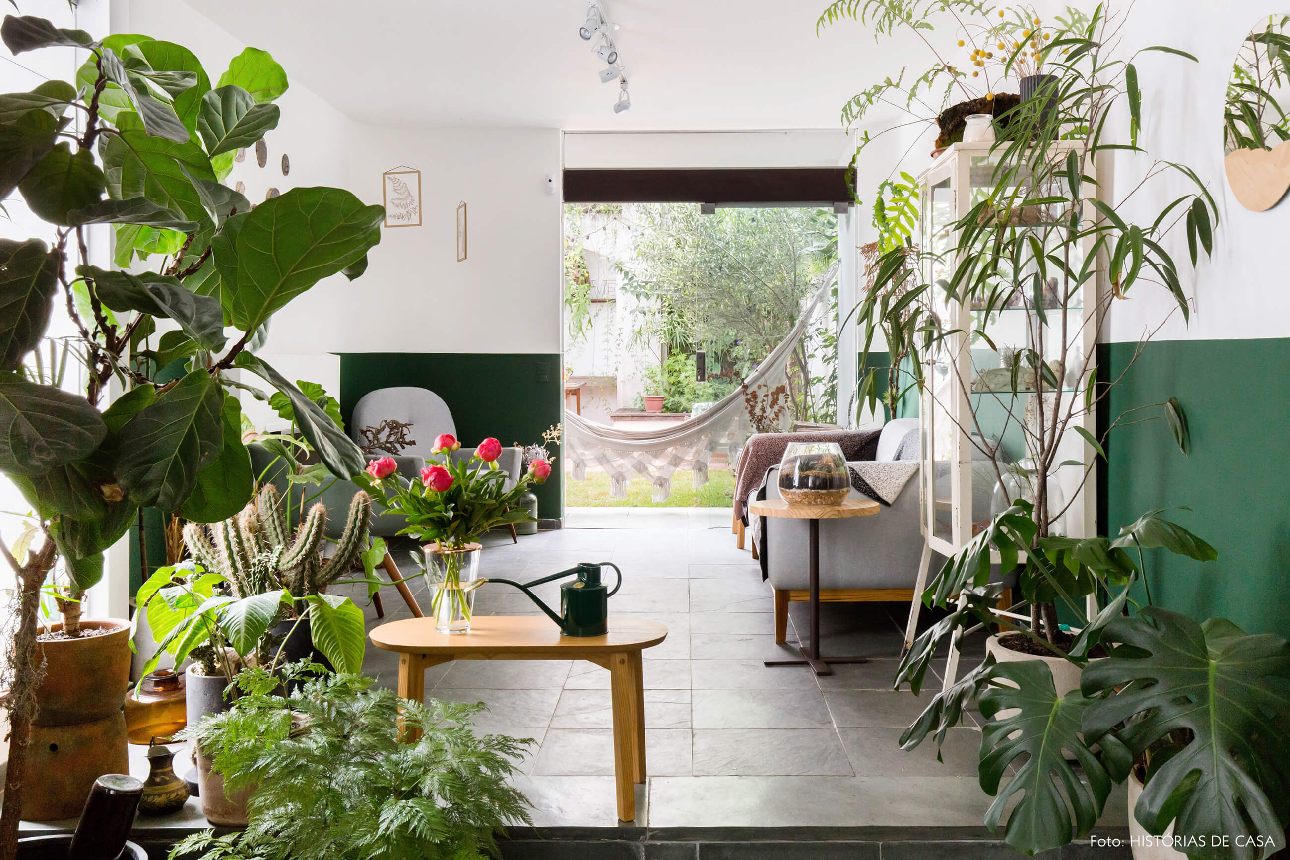 Sala com muitas plantas e piso cinza