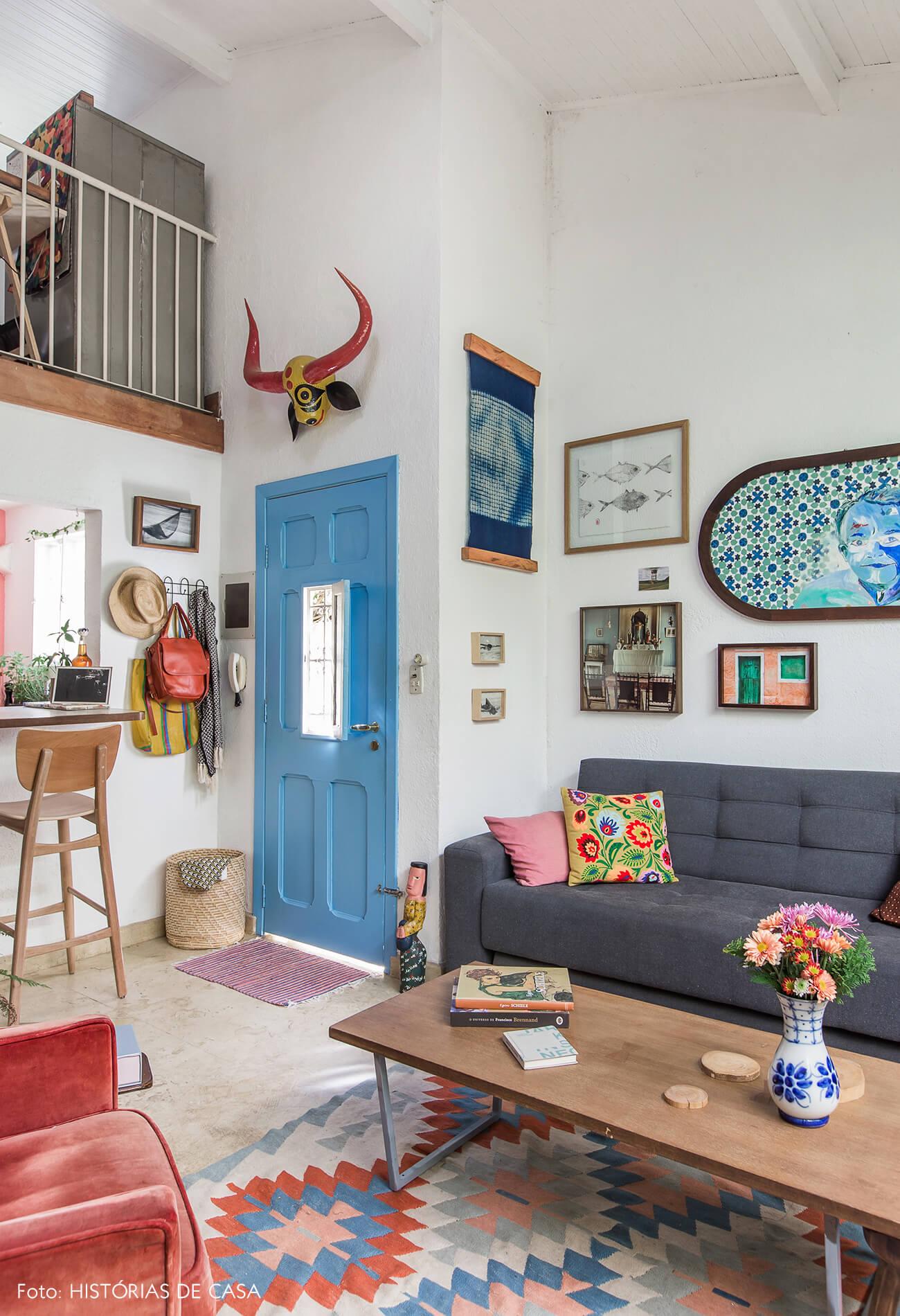 Sala com mezanino e porta pintada de azul