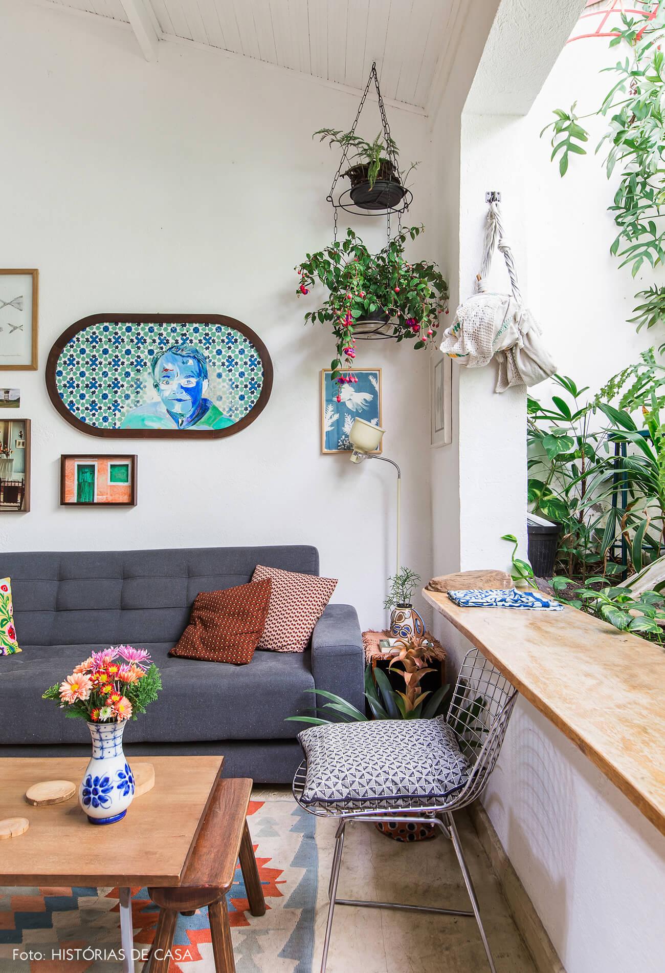 Sala com sofá cinza e jardim exuberante