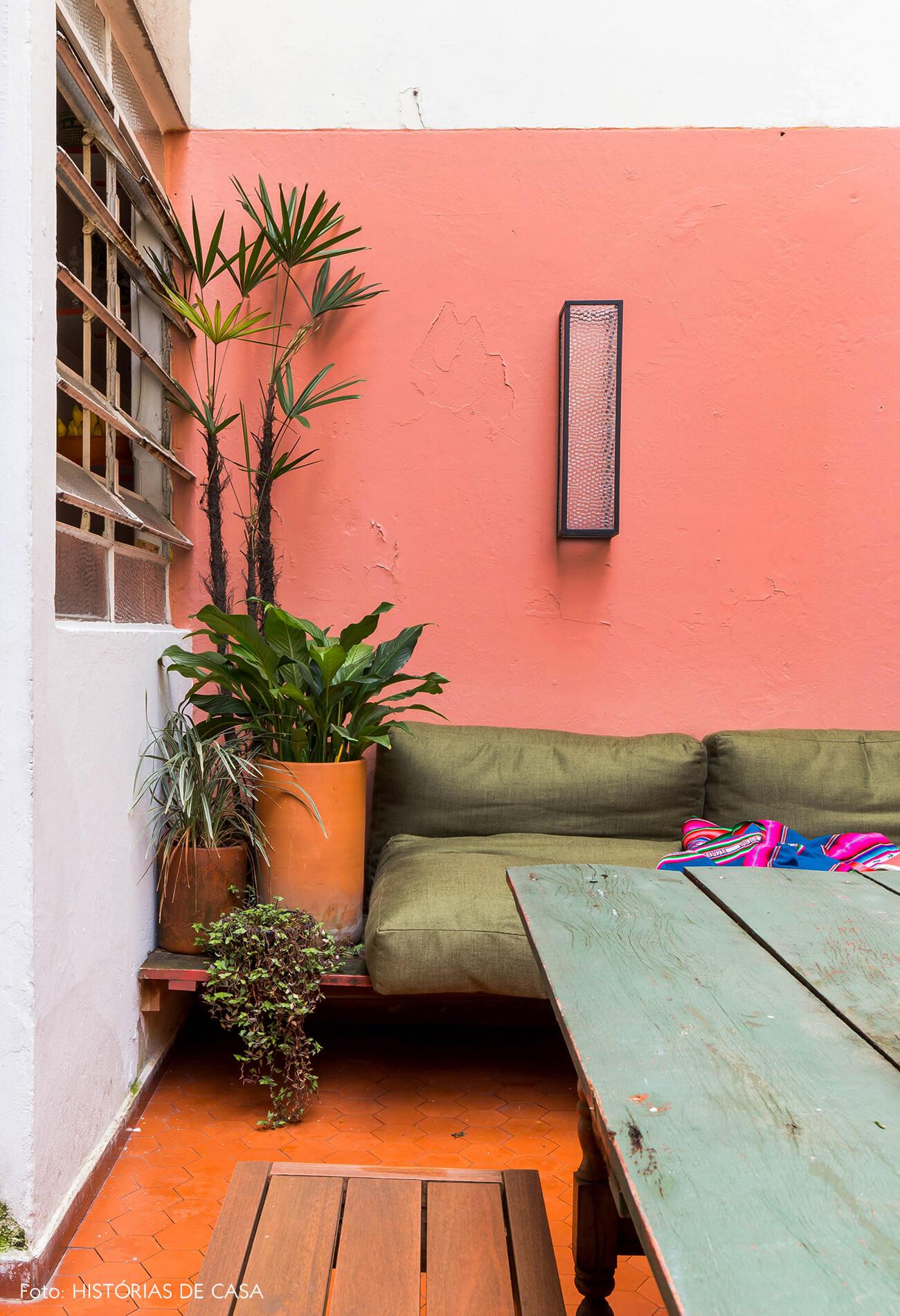 Quintal de apartamento com paredes coloridas e sofá verde
