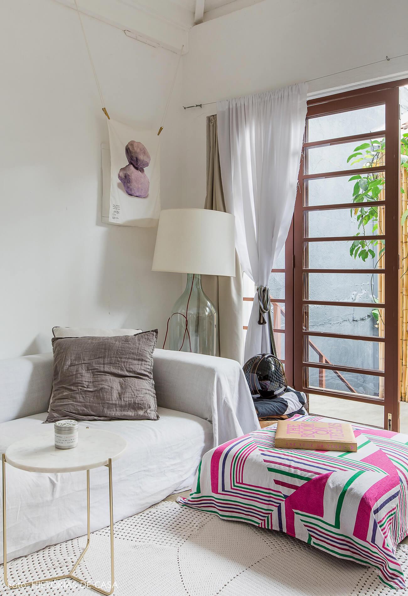 Sala com sofá branco com capa e pufe estampado