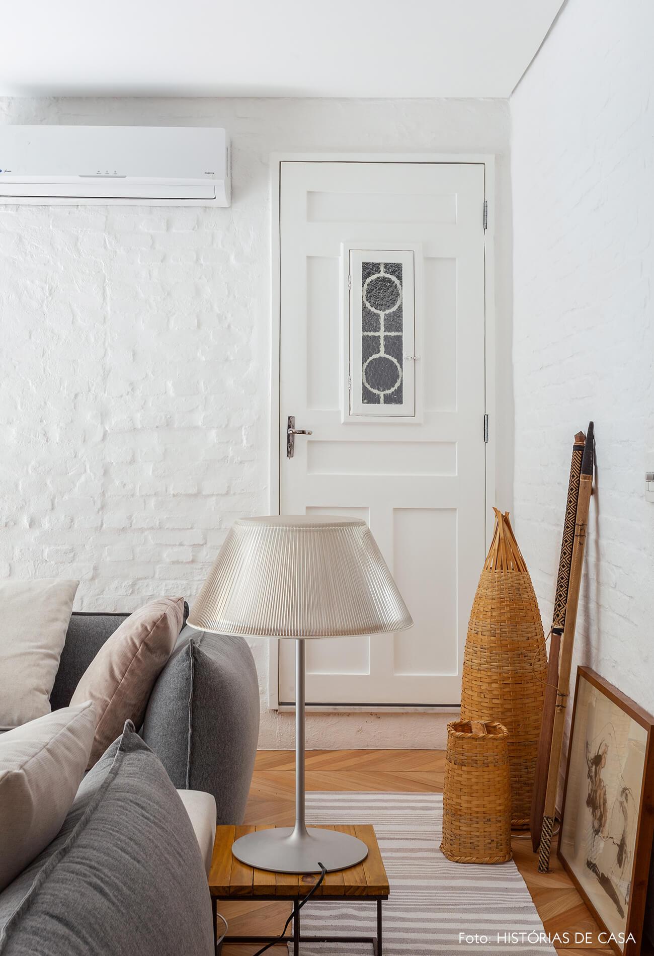 Sala integrada com tijolinho branco e sofá cinza