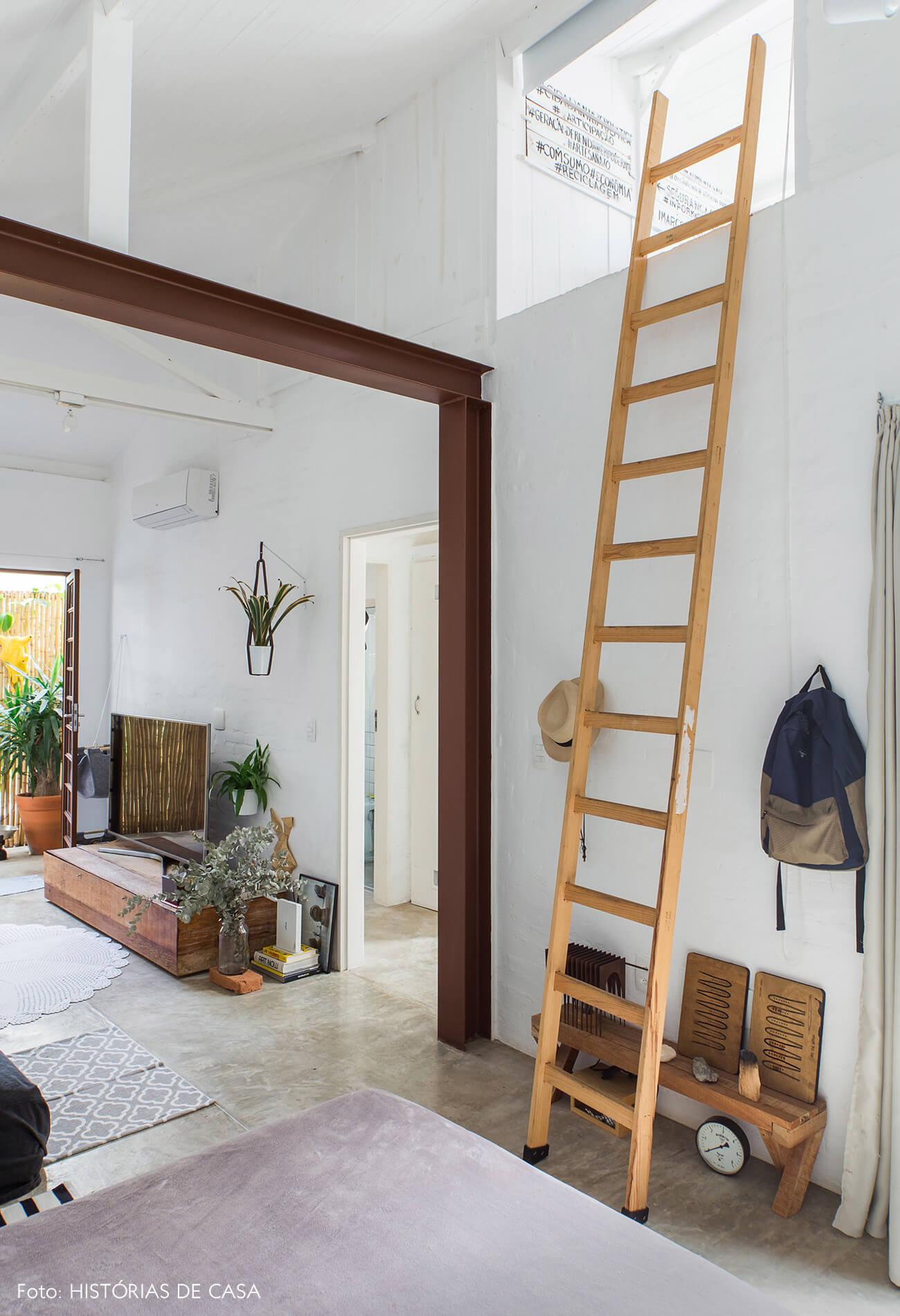 Sala com pé-direito alto e escada de madeira