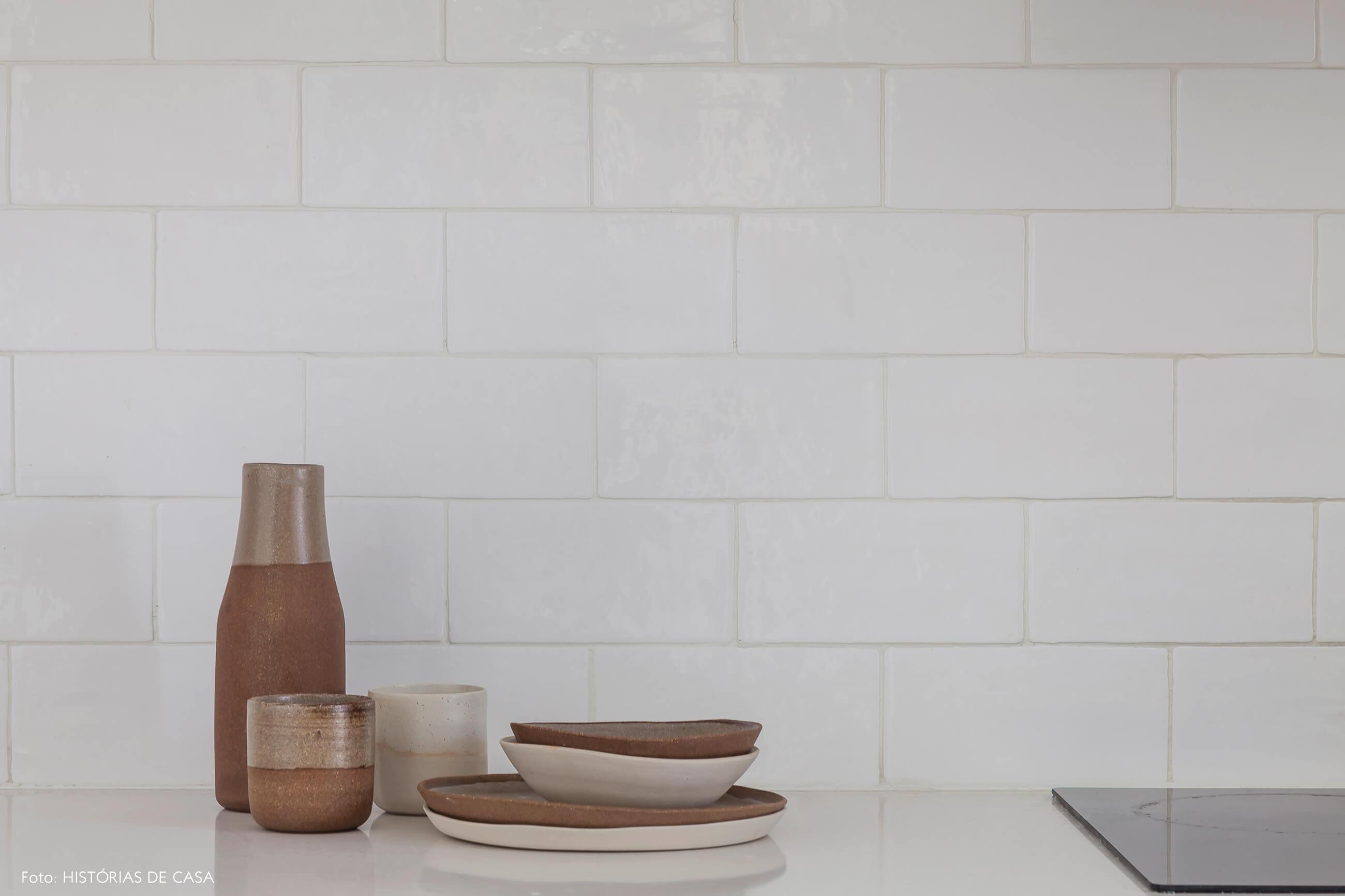 Parede com azulejos rústicos e peças de cerâmica