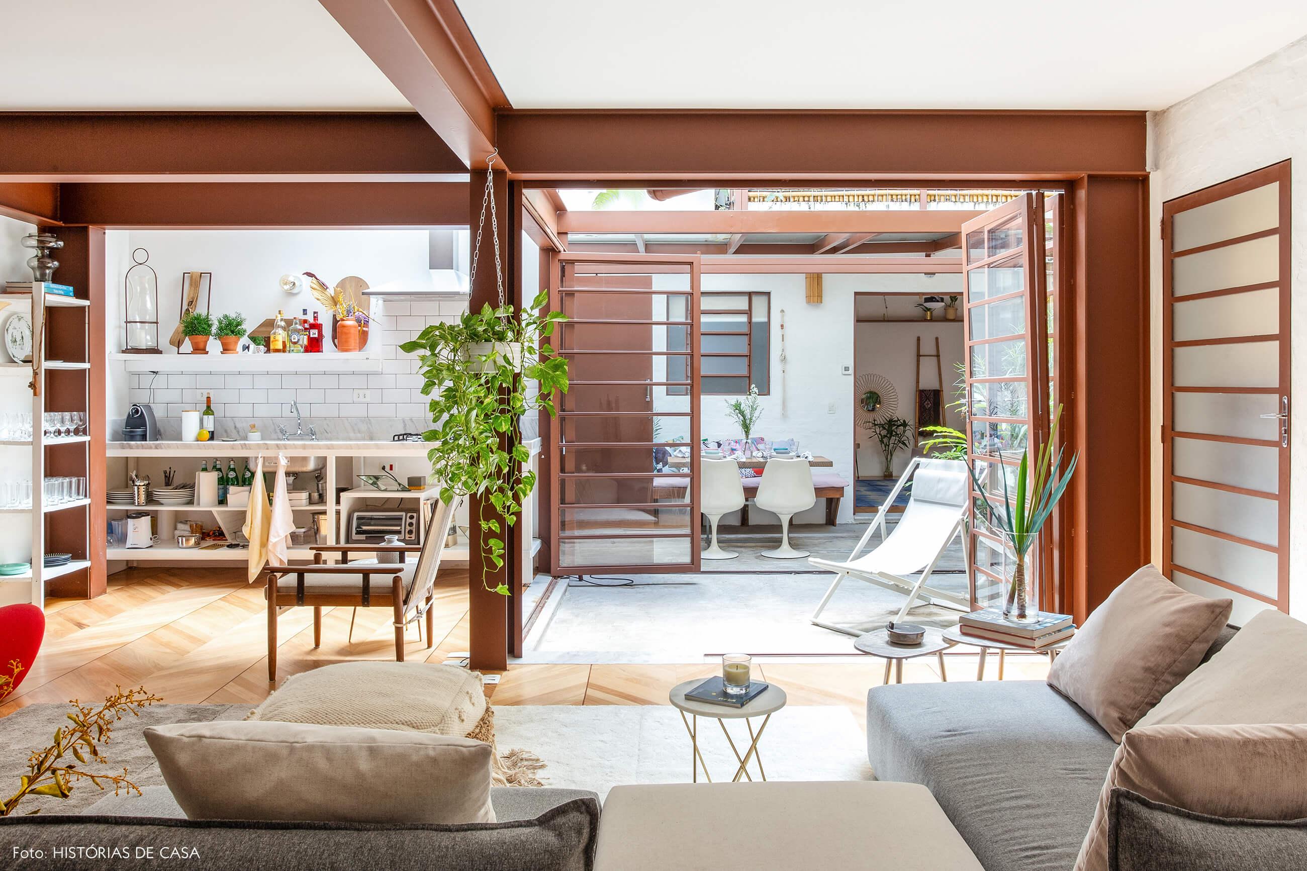 Sala integrada com vigas metálicas e jardim