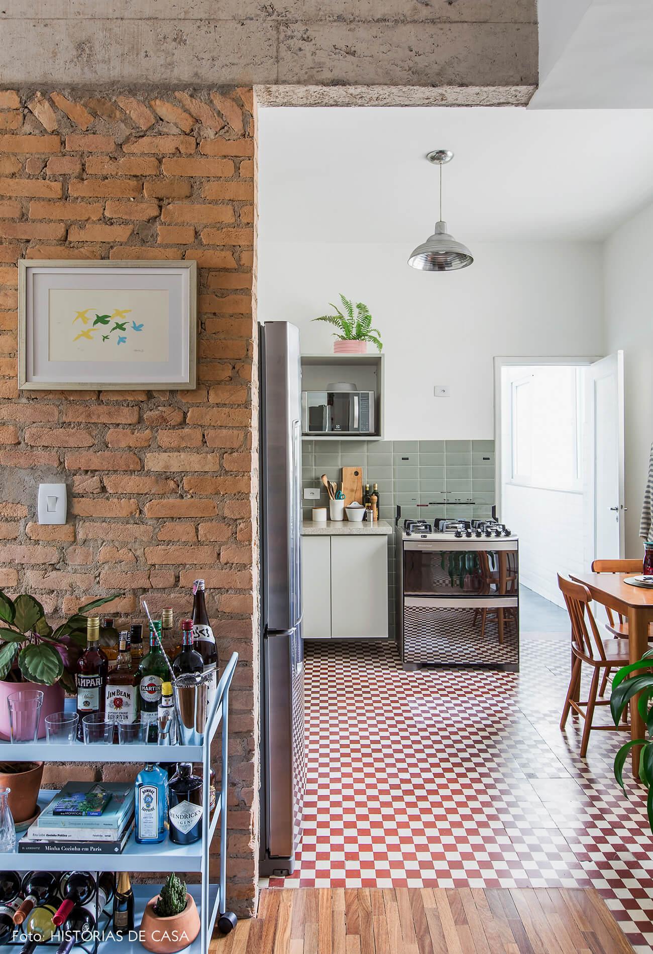 Apartamento reformado com cozinha integrada e parede de tijolinho