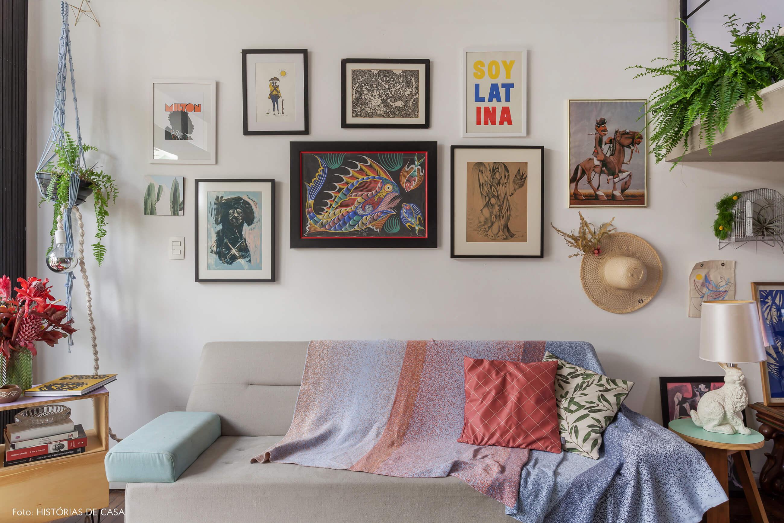 Sala com parede de quadros e sofá cinza