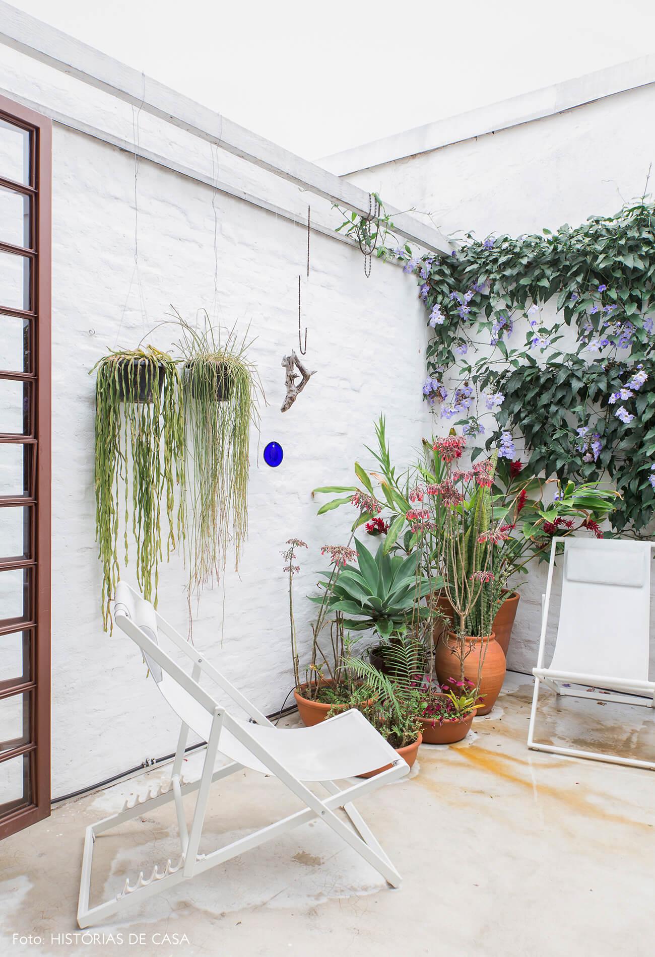 Quintal com parede rústica e espreguiçadeiras brancas